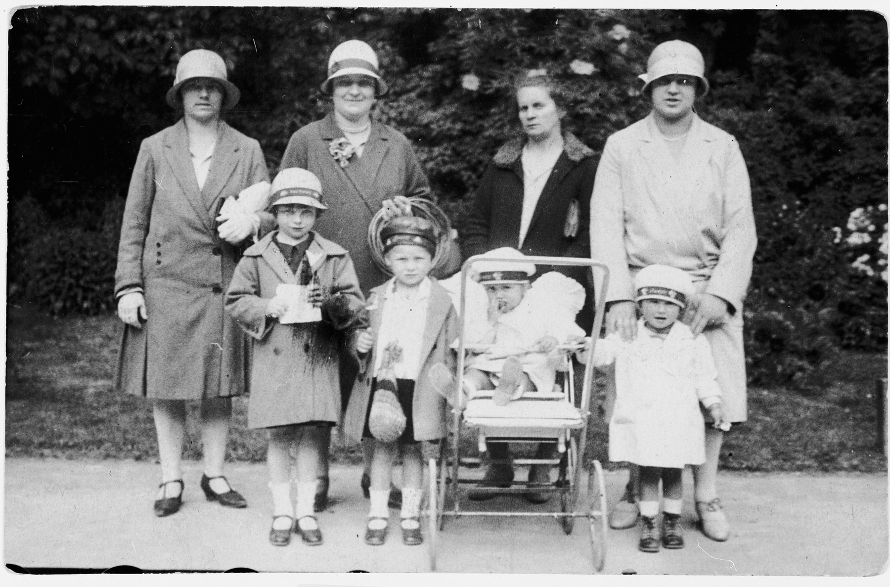 A group of mothers pose together in a park with their young children.  Pirsoka Rosenberger is on the far left with her hands on the shoulders of her daughter Judith.  Next to her is her nanny Marcelle pushing her younger daughter Olga in her stroller.