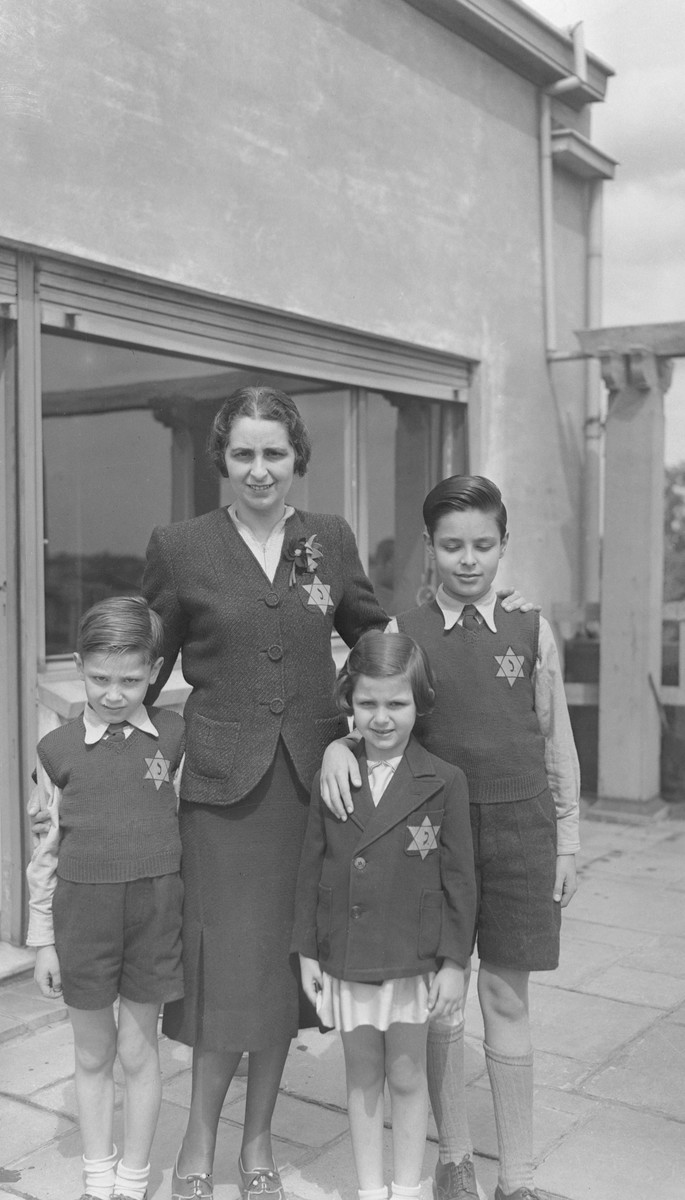 Portrait of a Belgian Jewish family wearing the yellow Star of David.  Pictured are Lucie Wellner and his three children, Marcel (right), Daniel (left) and Myriam (second from the right).