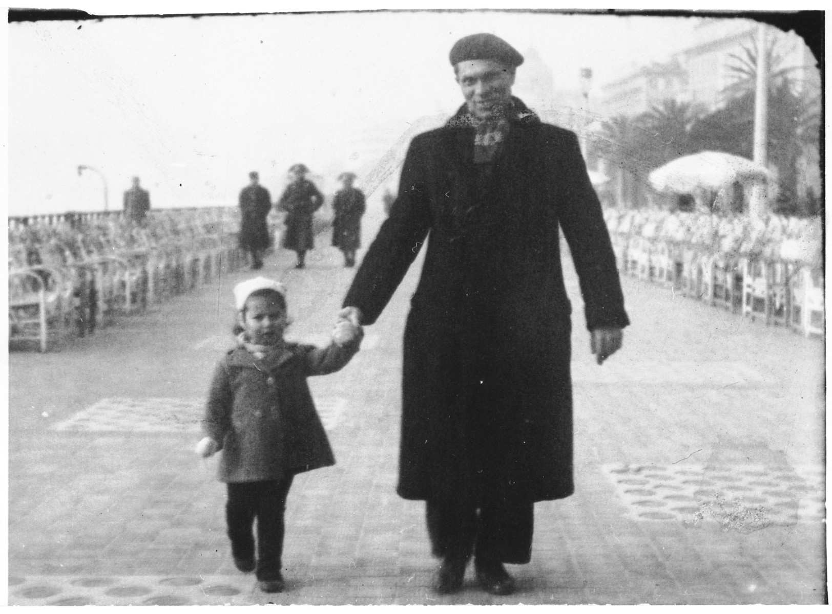 Esther Almer walks down the Promenade des Anglais in Nice holding her father's hand.
