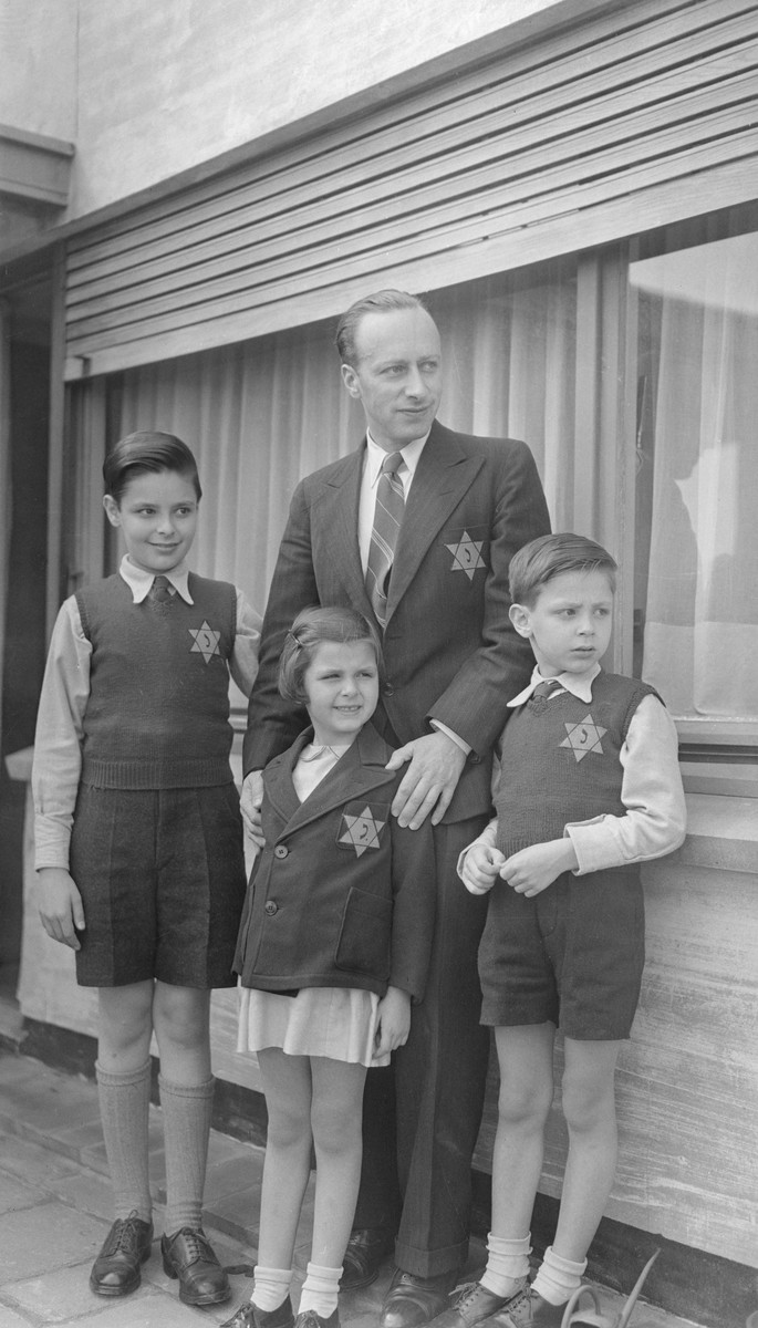 Portrait of a Belgian Jewish family wearing the yellow Star of David.  Pictured are Jules Wellner and his three children, Marcel (left), Daniel (right) and Myriam (center).