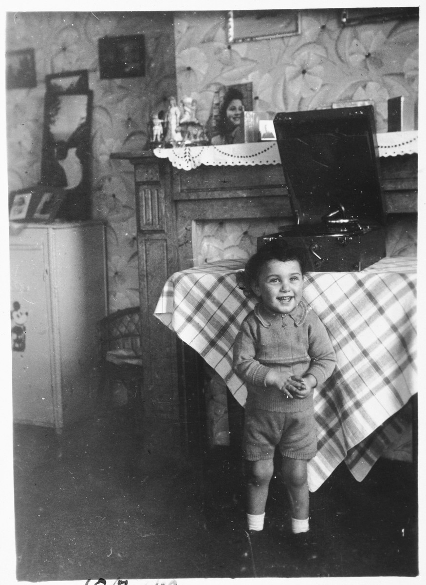 A young Jewish boy listens to the music of a phonograph while living in hiding as a Christian in Brussels.  Pictured is Nathan (Nounou) Ciechanow.  He was subsequently deported to his death in Auschwitz.