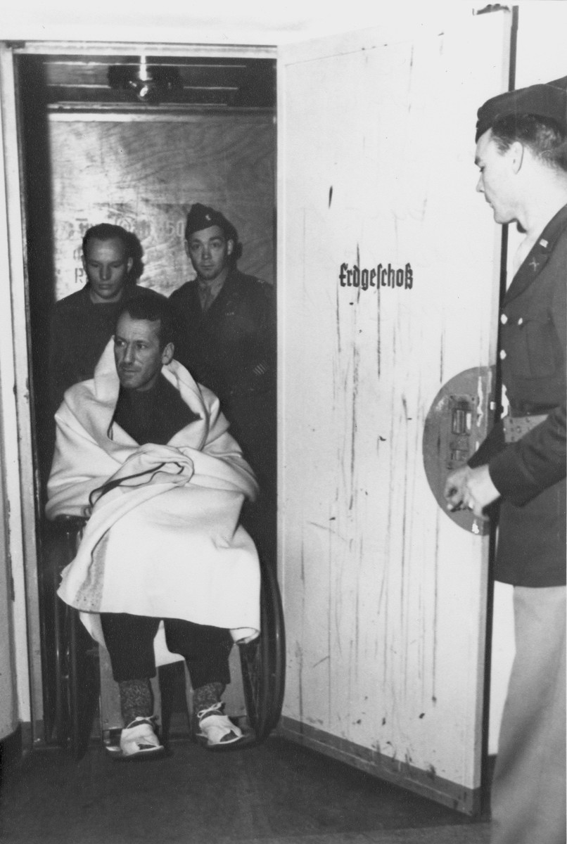 Two military policeman escort Nuremberg defendant, SS General Ernst Kaltenbrunner in a wheelchair to the courtroom.  Kaltenbrunner was recovering from a cranial hemmorage.