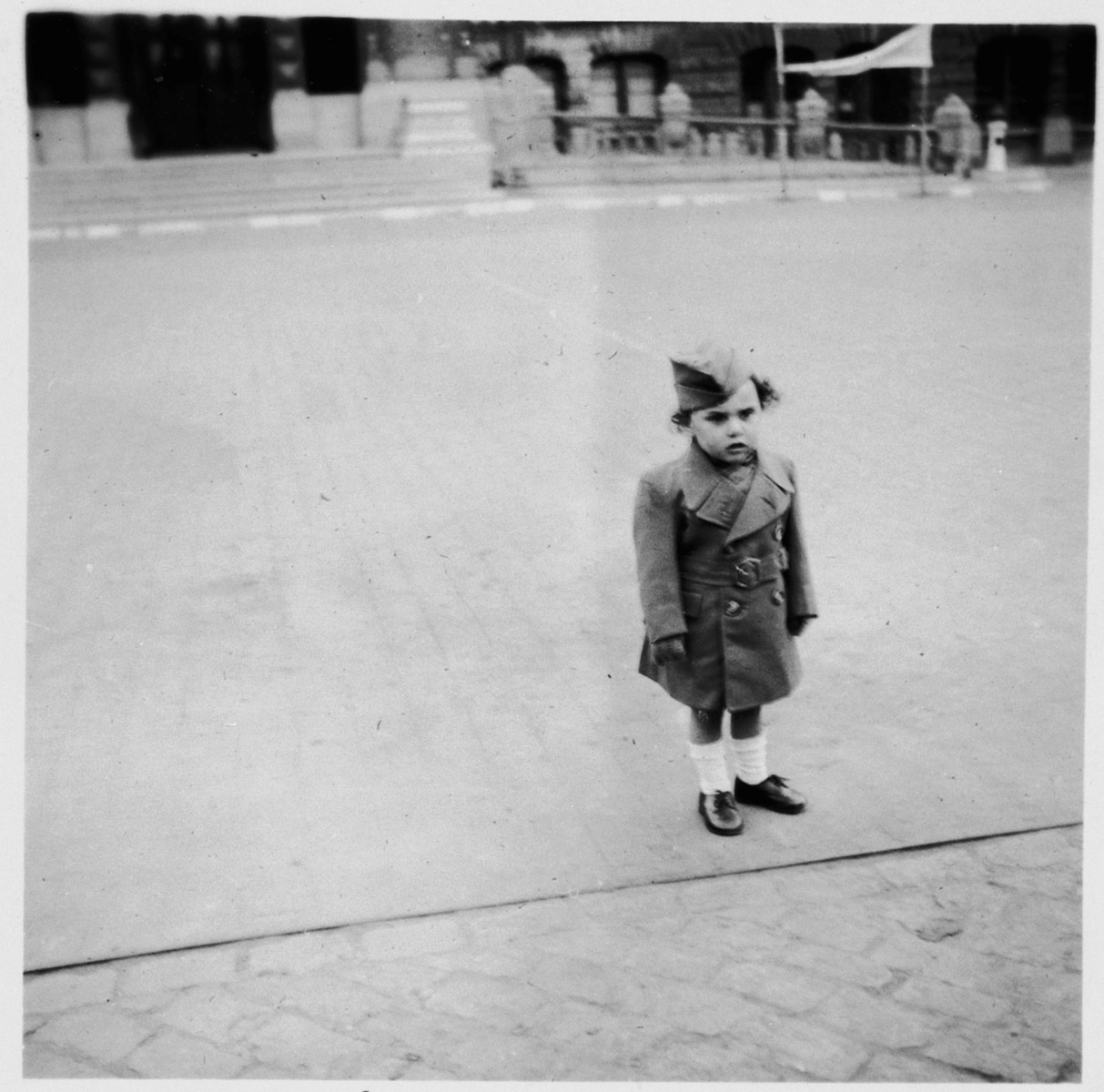 A young Jewish boy poses on a sidewalk in Brussels, near the apartment where he is living in hiding as a Christian with his parents.  Pictured is Nathan (Nounou) Ciechanow.  He was subsequently deported to his death in Auschwitz.