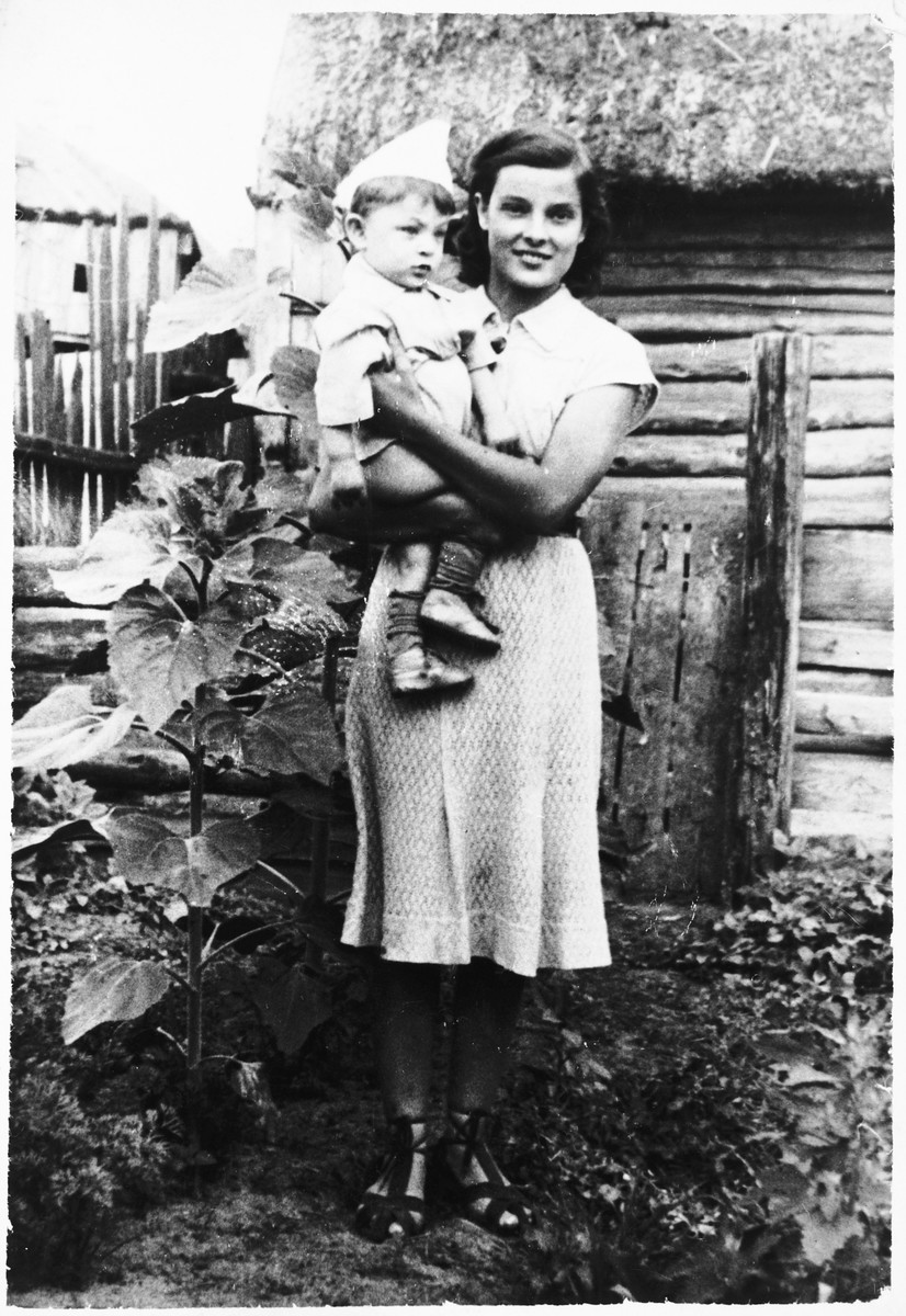 Faigel holds her nephew Schelemale, the son of her older brother Moishe.  The photograph was taken by Moishe who ran a photography studio.