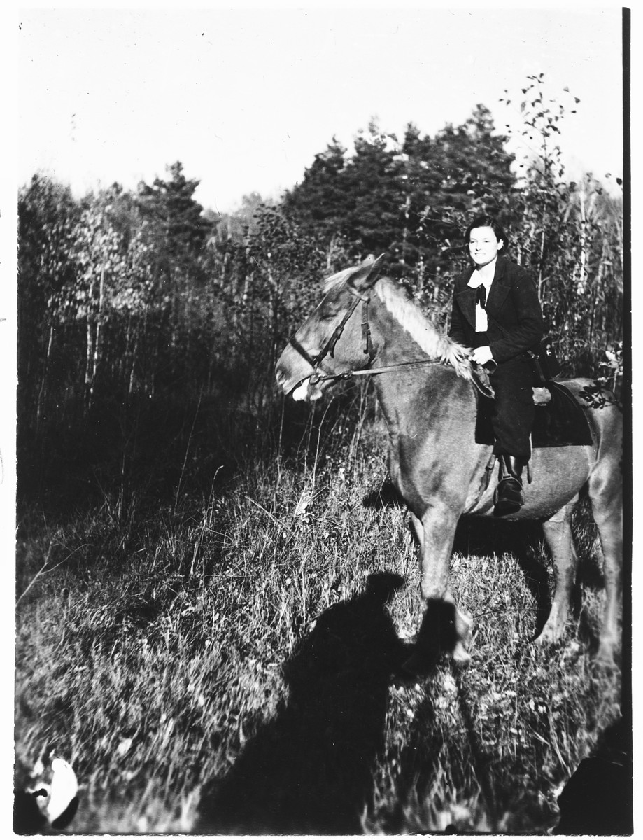Faigel Lazebnik poses while on horseback.  She set up the camera and tripod (the shadow of which can be seen in the foreground) and had a friend shoot the photograph.