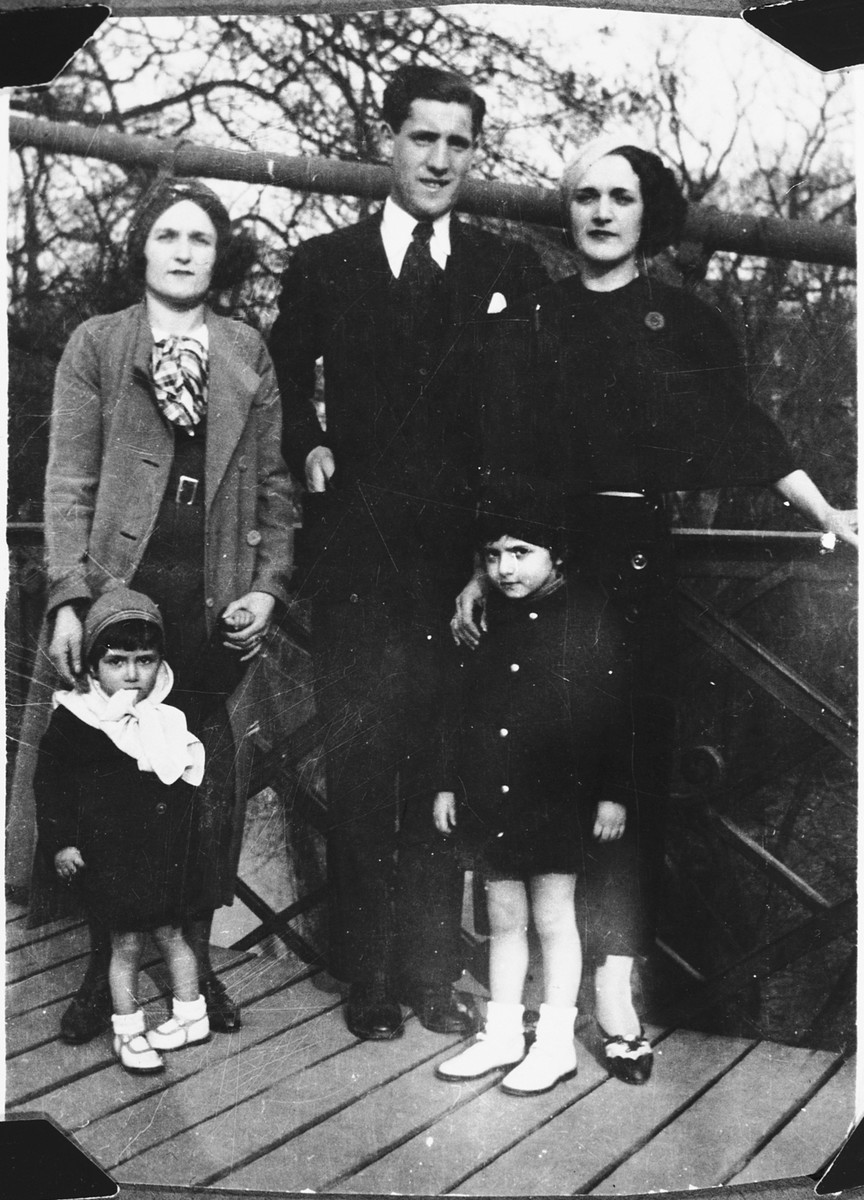 Members of an extended Jewish family pose on an outing to a park in Antwerp, Belgium.  Pictured behind from right to left are: Fani Mendelowicz, an unnamed cousin, and Fani's sister, Leah In front of them are Flora (right) and Charlotte (left) Mendelowicz.