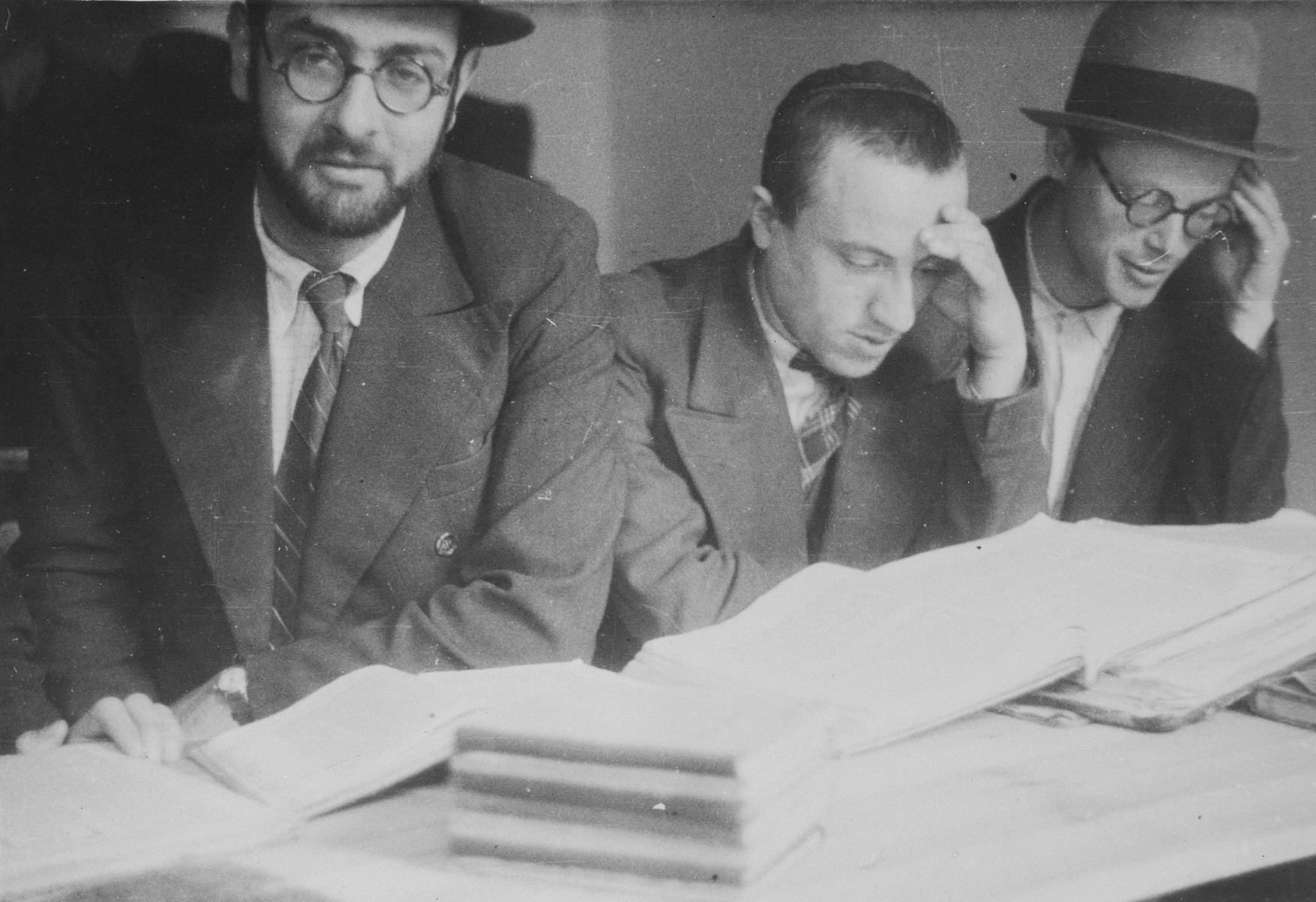 Students at the Mir Yeshiva in Kobe study around a table.  Elchanan Yosef Hertzman is on the right and Boruch Yaakov Alter is in the middle.