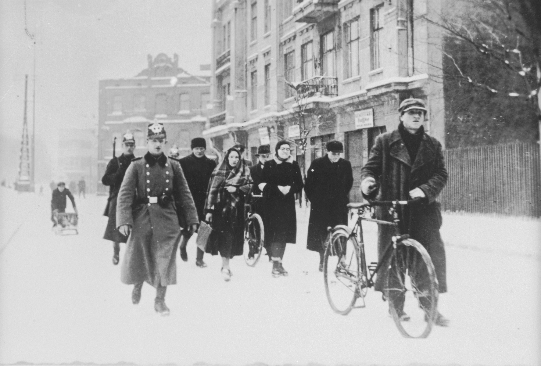 German police escort a group of Jews along a snow covered street during a deportation action in Zawiercie.