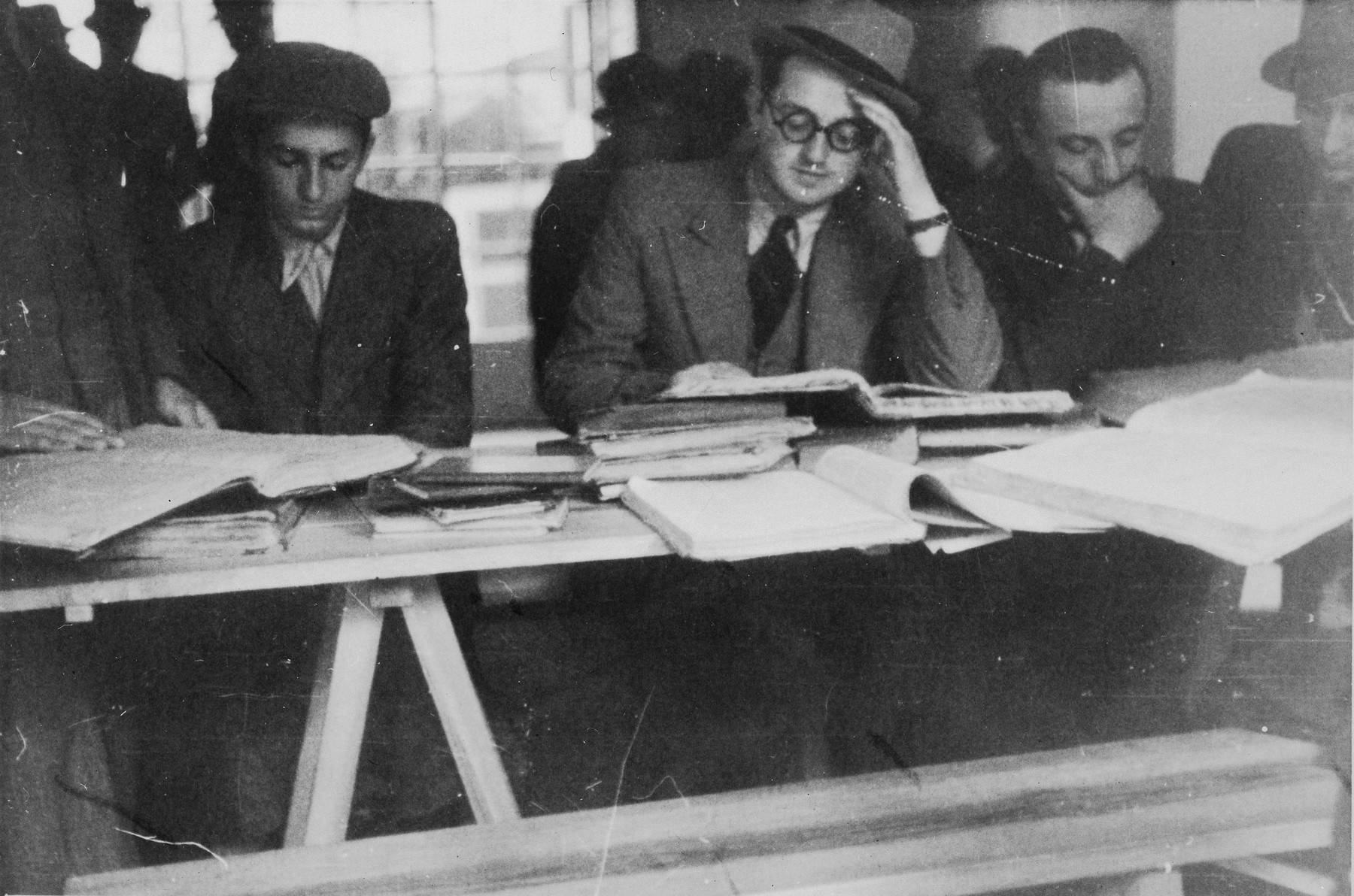 Students at the Mir Yeshiva in Kobe study around a table.  Rabbi Avraham Blumenkrantz is seated in the center and on the far right is Boruch Yaakov Alter.