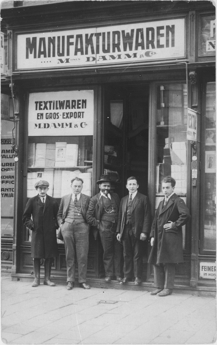 Jewish owners and employees of the M. Damm textile company in Vienna pose in front of their business.  Pictured from right to left are: Hermann Herzmann, Baruch Brenig, Mr. Damm (Baruch's business partner), Mr. Brummer, and an unidentified employee.