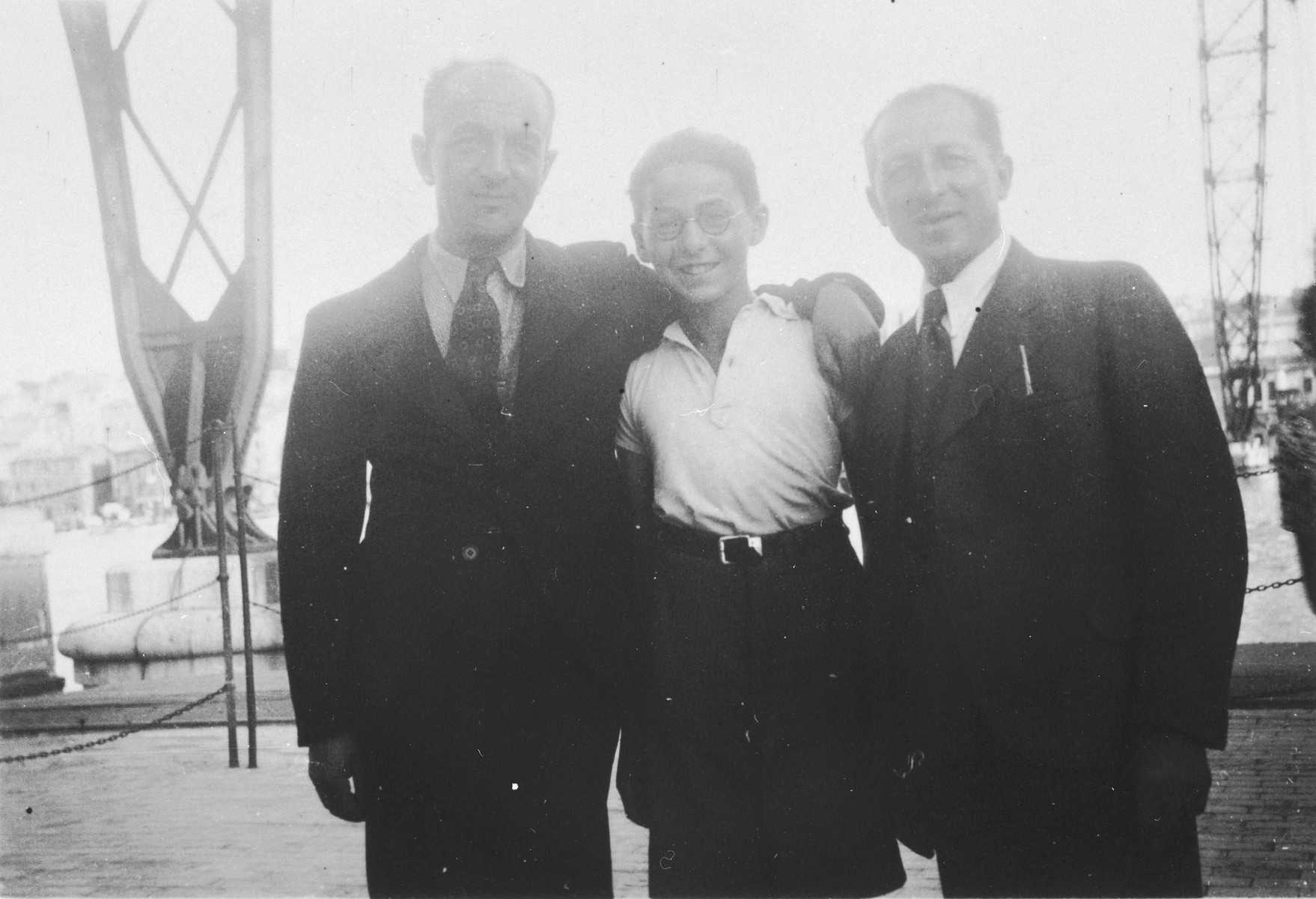 During a temporary leave from the Les Milles internment camp, Baruch Brenig (right) poses with his son,Theo (center), and brother-in-law, Hermann Herzmann (left), at the Vieux Port in Marseilles.  Baruch was given a temporary leave from the Les Milles internment camp in order to arrange for the emigration of his family.