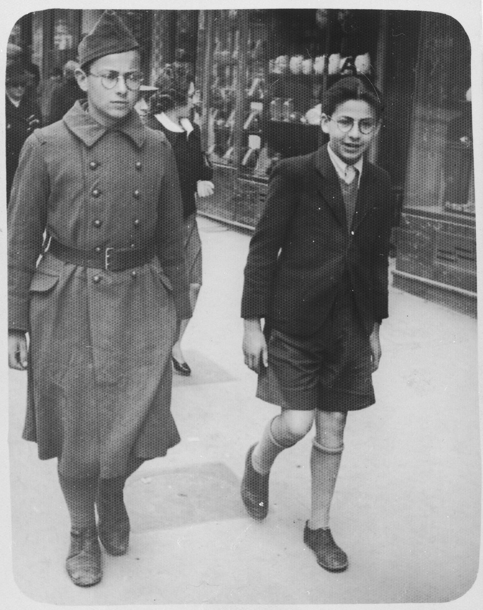 Two Jewish refugee brothers walk down a street in Marseilles.  Pictured are Theo Brenig (right) and his brother, Joseph (left).
