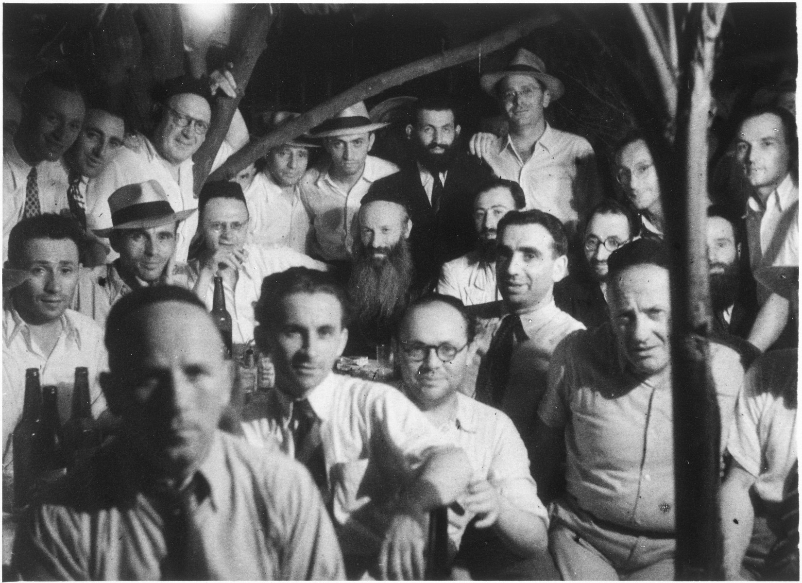 A group of Jewish refugee yeshiva students in Shanghai gather around Rabbi Samuel Walkin, the former rebbe of Lukatz Kreuz (near Poznan).  Rabbi Walkin is pictured in the center (with the long beard).  Pictured in the back row, center with a hat is Samuel Chaim Soroka.