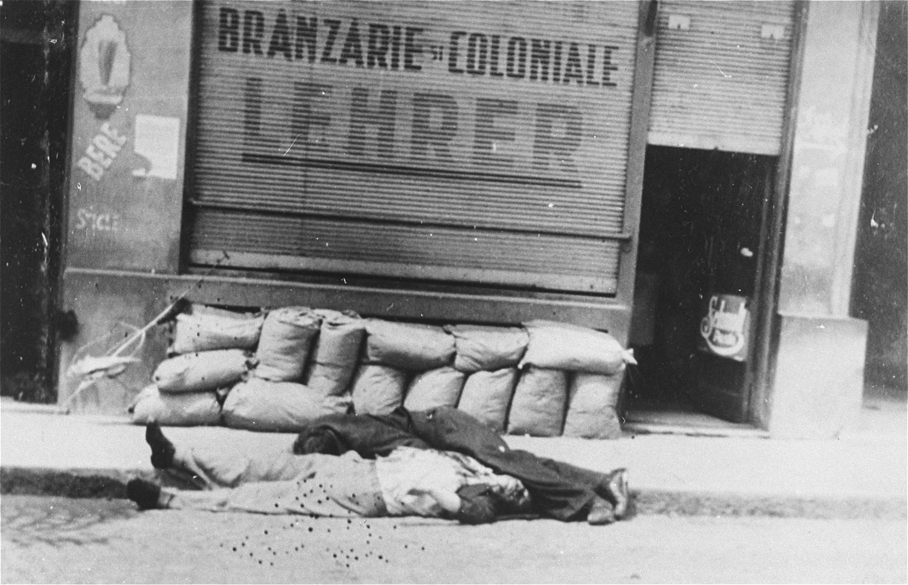 The bodies of Jews killed during the Iasi pogrom lie on the pavement in front of a Jewish-owned business.
