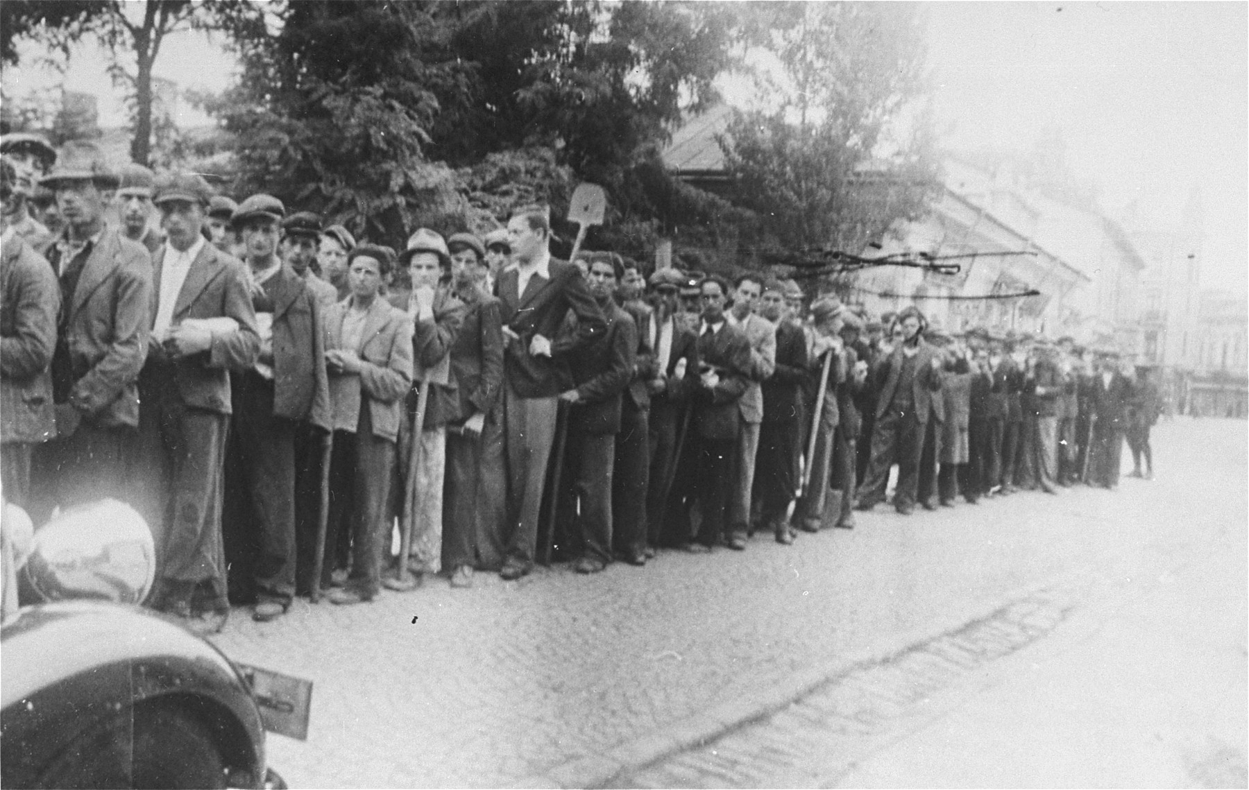 A column of young Jewish men, who had been conscripted by the Romanian authorities for forced labor (digging shelters or mass graves in the Jewish cemetery), are brought to police headquarters during the Iasi pogrom.  The common pits dug at this time became the graves of many Jews murdered during the Iasi pogrom.