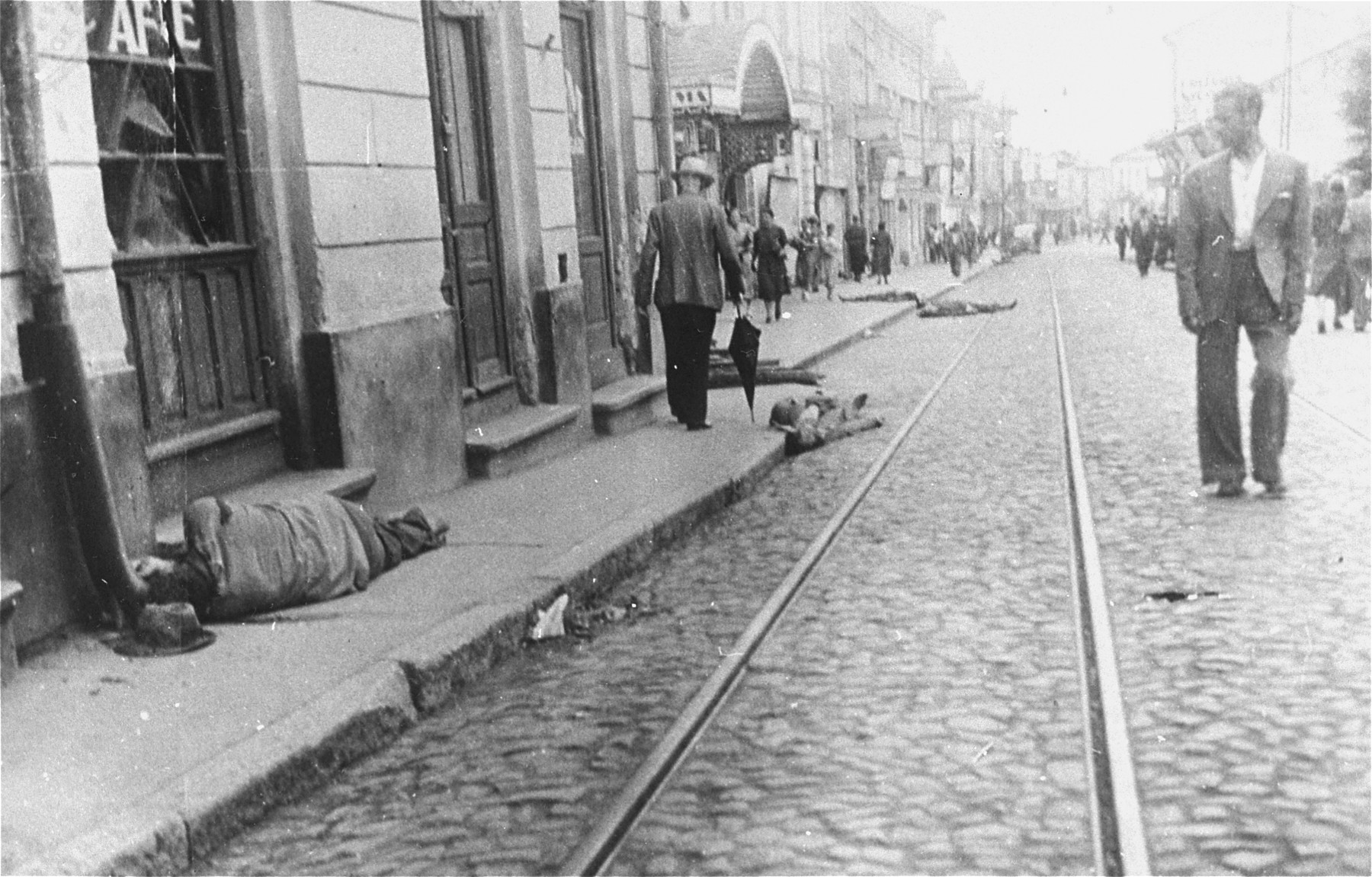 Civilians walk along Cuza Voda Street in central Iasi, near the Cinema Sidoli, past the bodies of Jews killed by Romanian soldiers and civilians during the Iasi pogrom.
