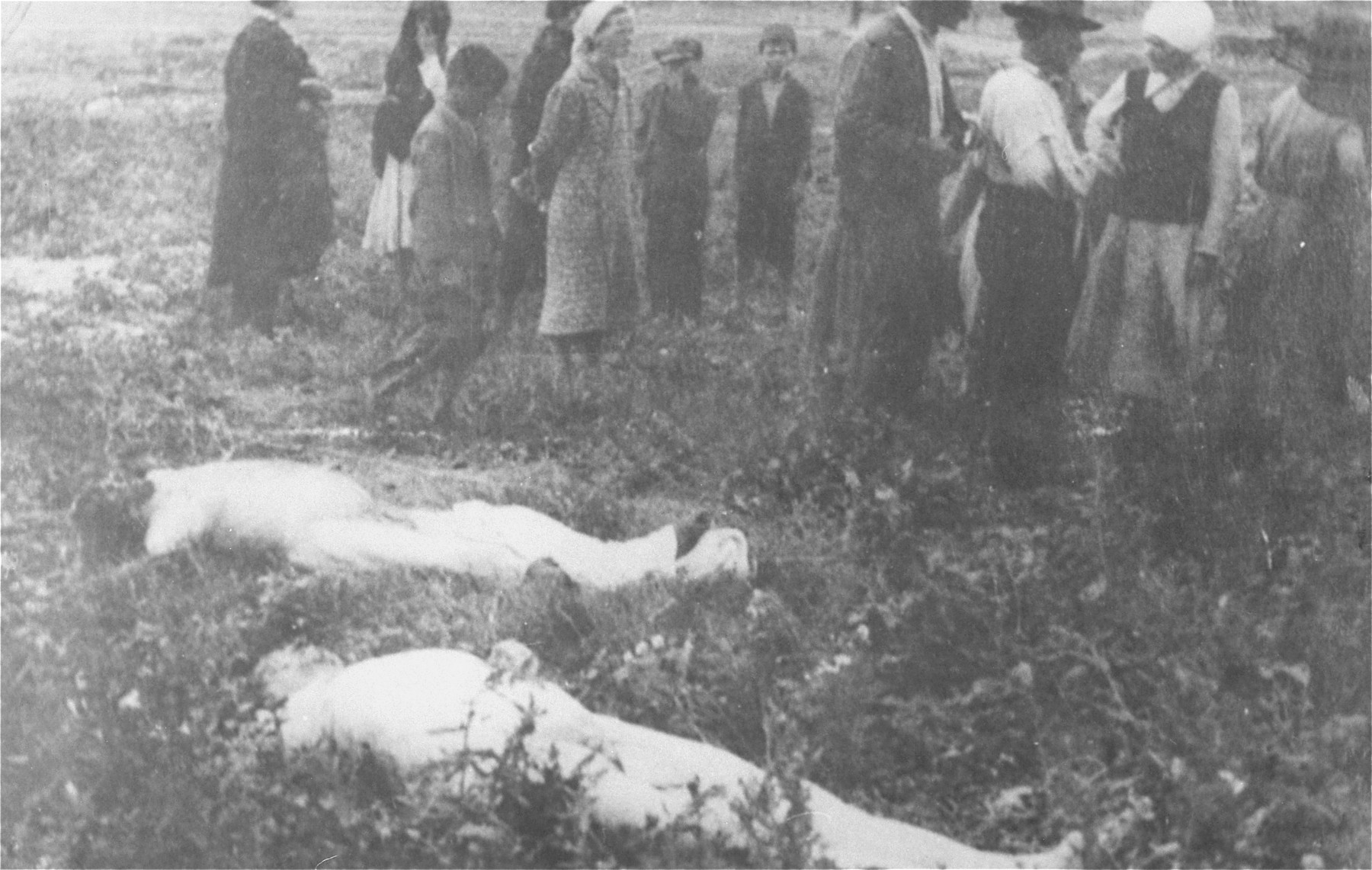 Civilians walk among the bodies that have been removed from the Iasi death train.