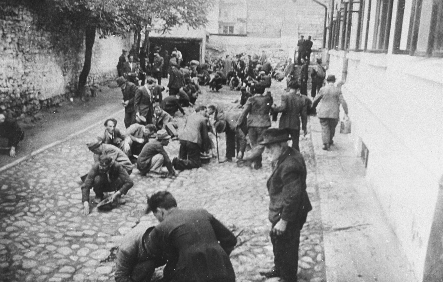 Jews are forced to clean blood from the cobblestone pavement of the Iasi police headquarters courtyard during the pogrom.
