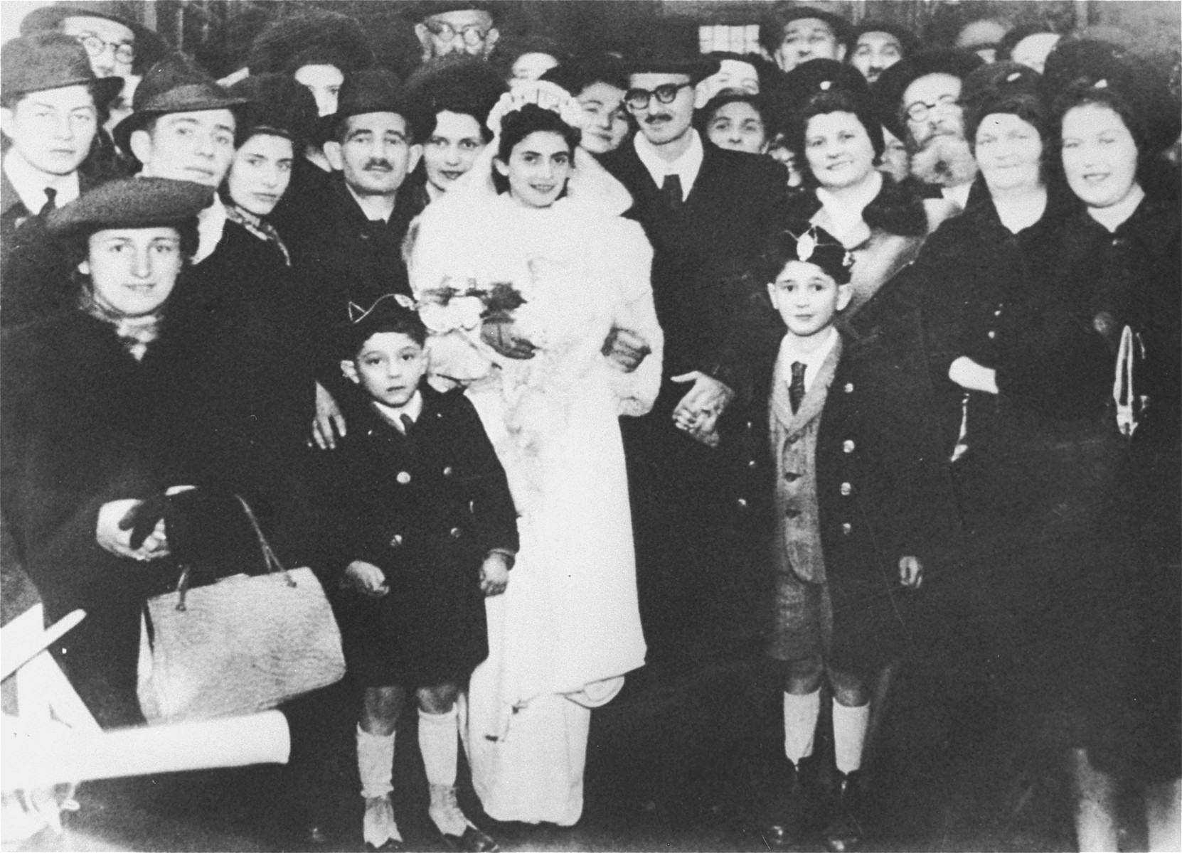 Group portrait of members of a Jewish wedding party in Bucharest.  Among those pictured is the bride, Grete Kleinman.  Her father stands next to her on the left.  Her brother, Eugene Kleinman, stands in the second row from the top, second from the left.  Eugene Woolrich stands in the second row from the top at the far left.