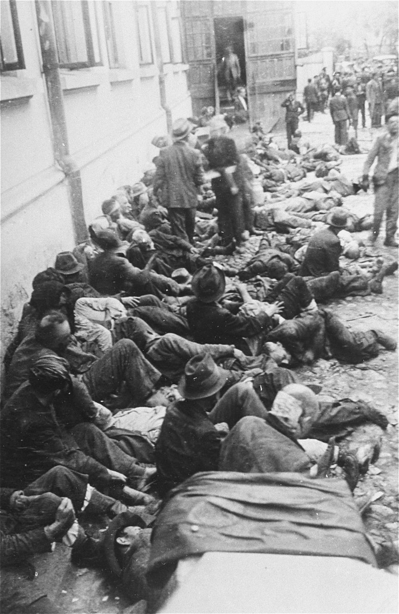 Jews assembled by Romanian police and soldiers during the Iasi pogrom sit among corpses in the courtyard of the city police headquarters.