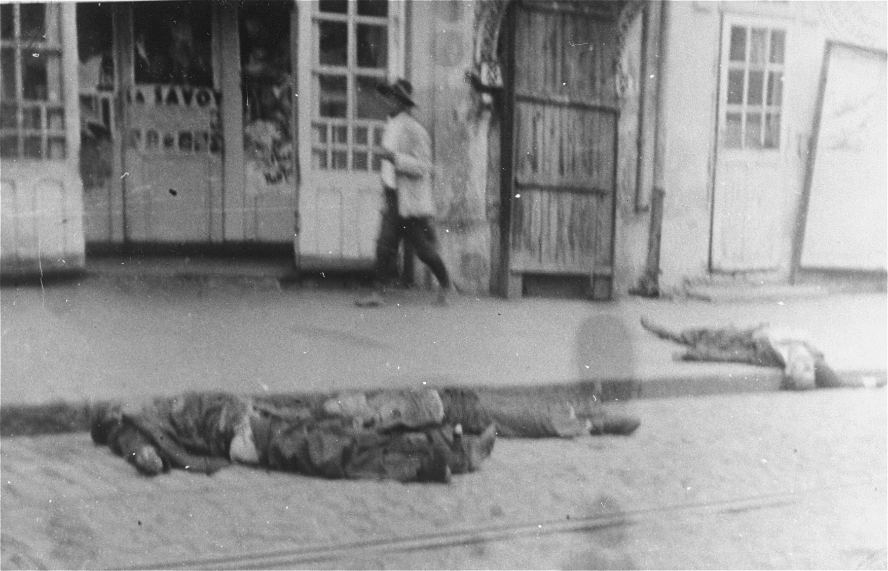 A Romanian civilian walks past the bodies of Jews killed on Cuza Voda Street during the Iasi pogrom.