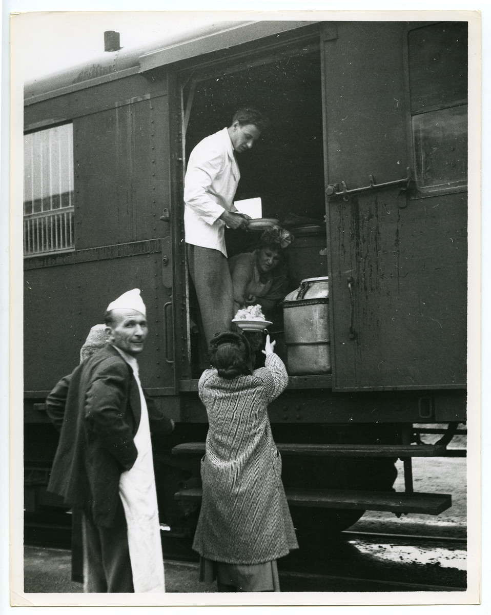 Displaced persons unload food supplies from a train.