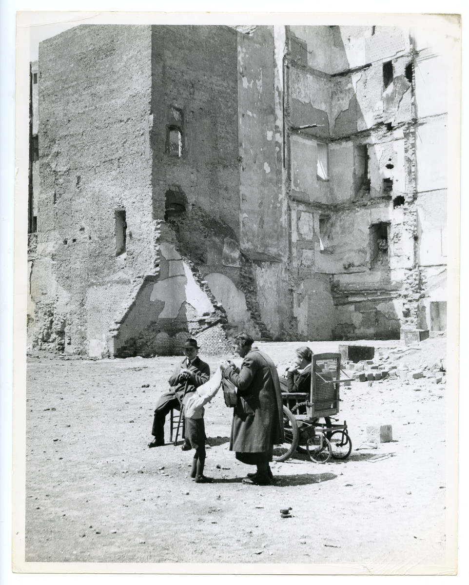 "A family relaxes in the sun amid war ruins in bombed-out Vienna,.  The photo's original caption reads: ""The Place in the Sun."""