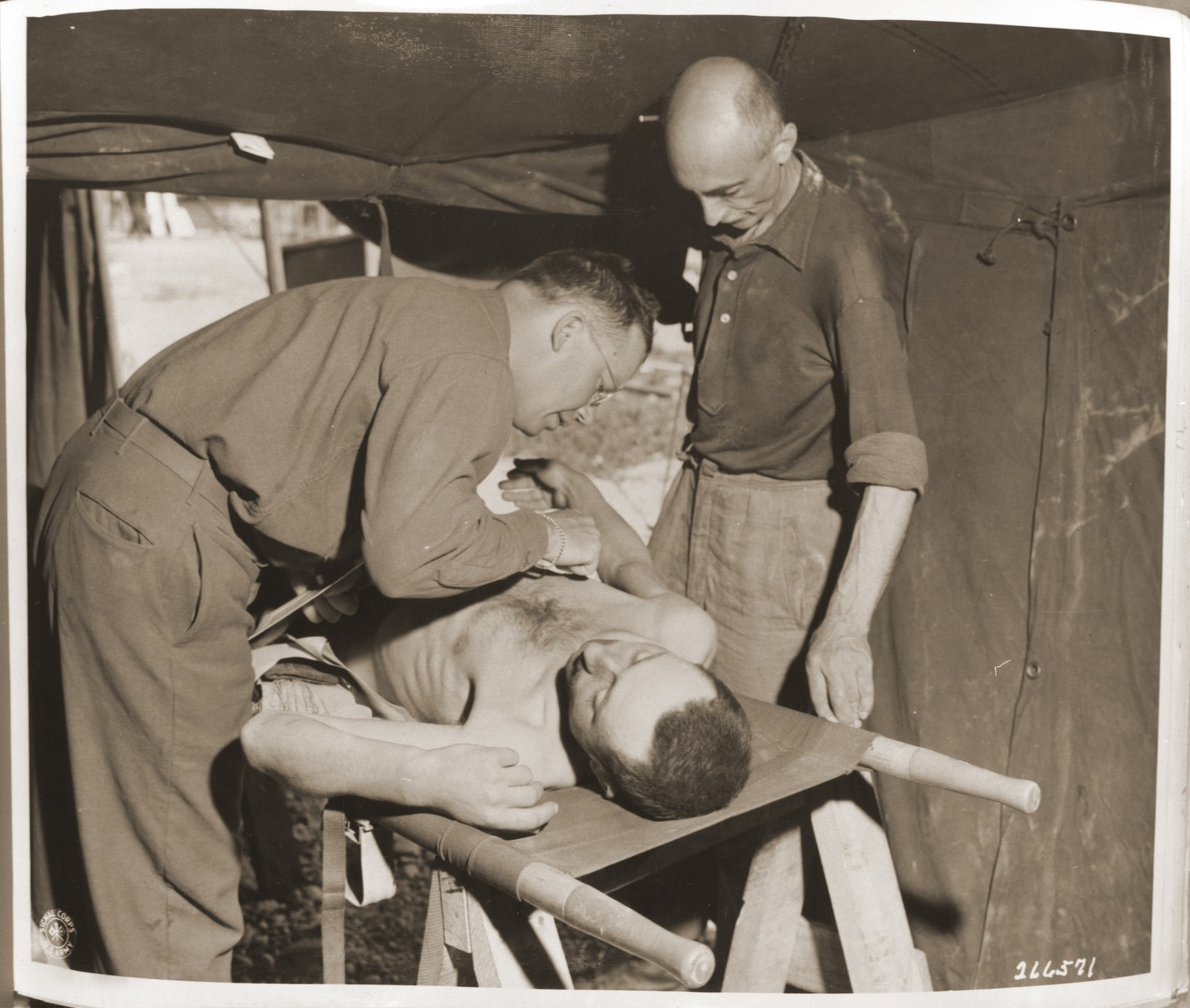 Captain Robert A. Baker of Newberry, S.C., gives medical attention to a former concentration camp prisoner suffering from malnutrition in an airport at Neubau.