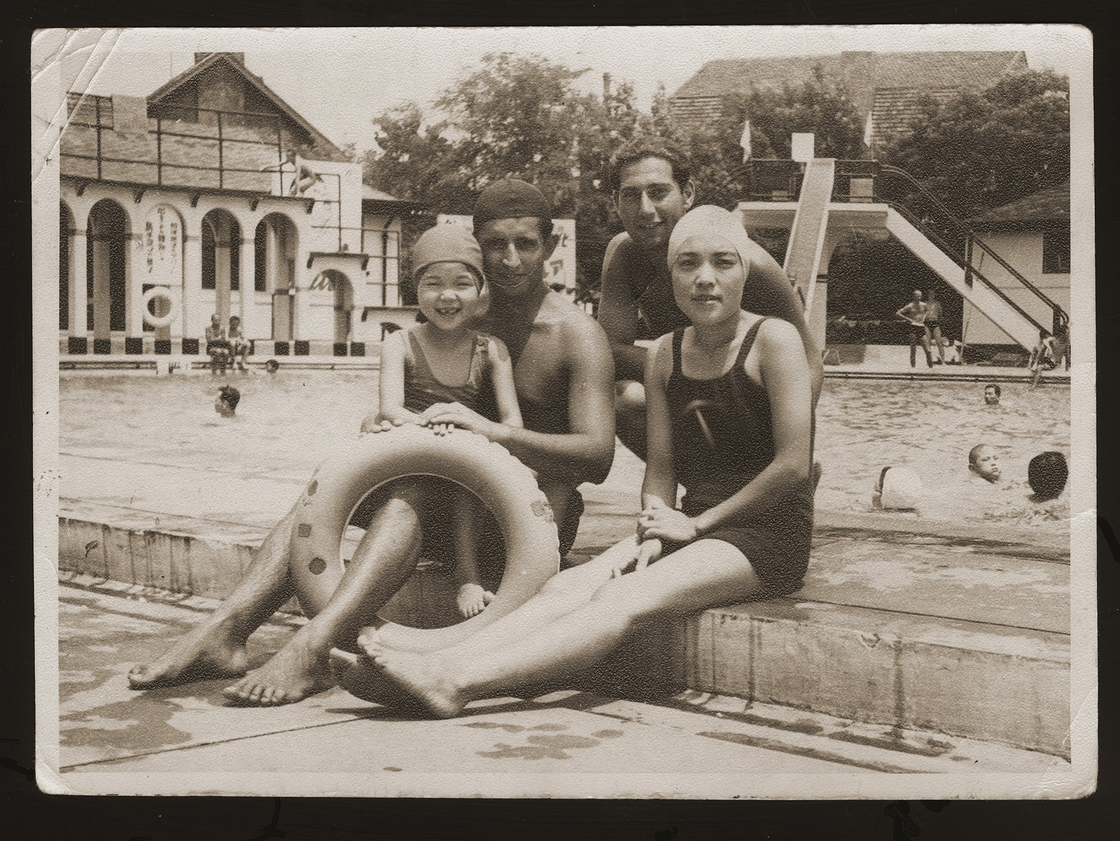 Peter Victor (second from right), a Jewish refugee from Berlin, with his friends Ely, Mrs. Oda, and her daughter at the Hongkew Park swimming pool.    Hongkew Park was a Japanese country club where Victor found employment as a lifeguard.