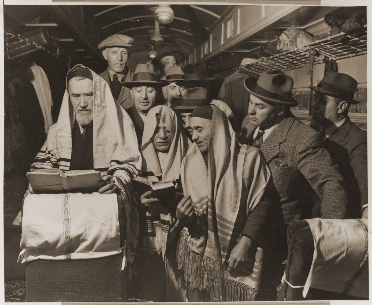 "Herman Auslander, left, a 75 year-old Jewish refugee from Shanghai, conducts a service on board the ""Liberty Train"" bound for Jersey City, NJ, from San Francisco.     The refugees on the train had previously travelled from Shanghai to California by ship.  From Jersey City they were transferred to Ellis Island for several days before continuing on to Israel by  U.S. Army transport."