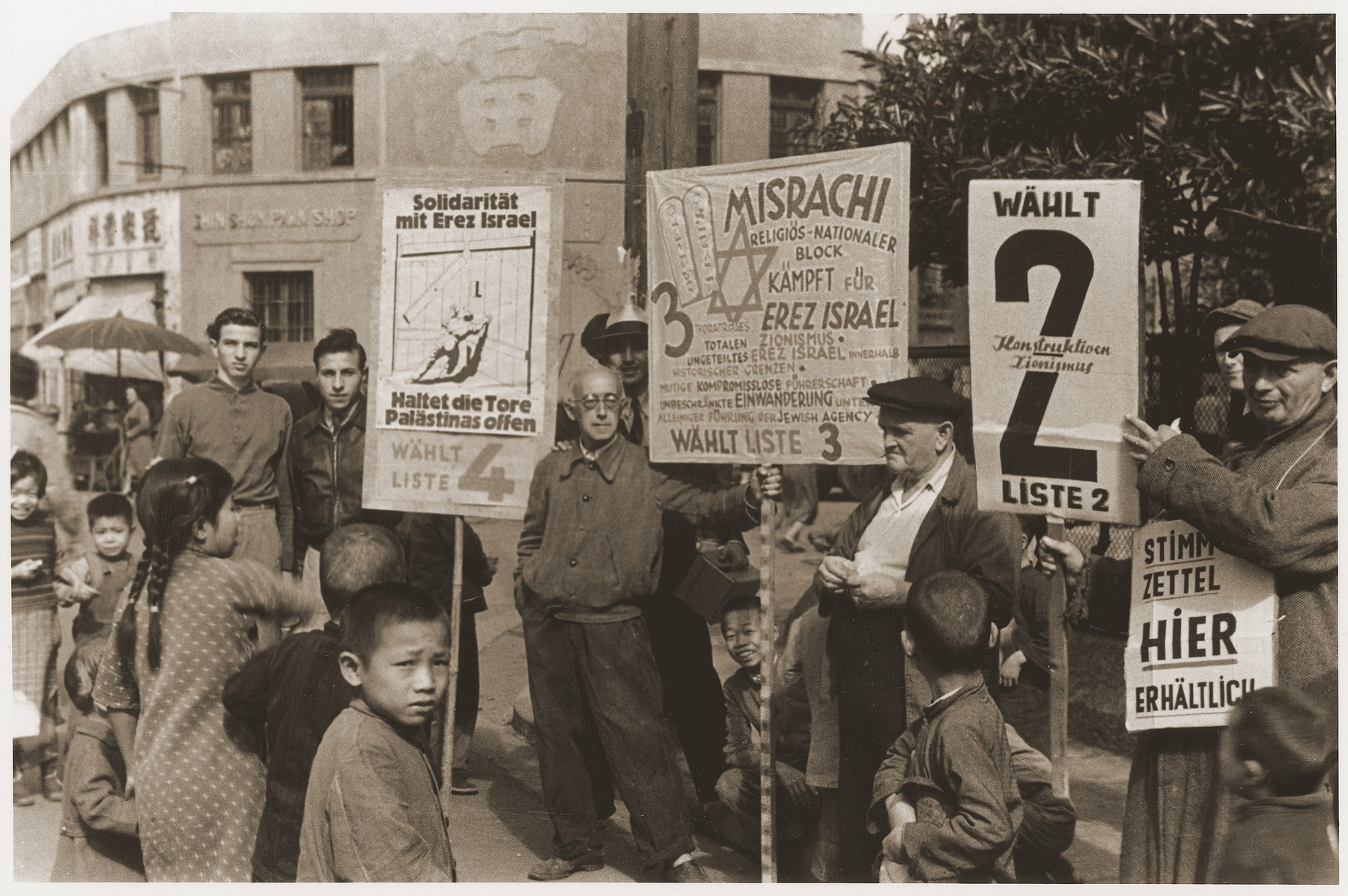 Jewish refugees hold up signs in German during an electoral campaign for an unidentified Zionist representative body.