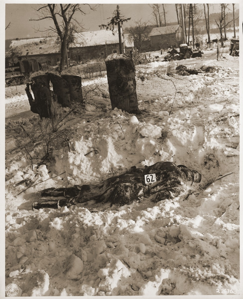 "The corpse of an American soldier killed by the SS in the Malmedy atrocity.  The original caption reads ""American soldiers were shot by German troops after they had surrendered were left where they had fallen in the snow.  Barbed wire is conspicuous where this soldier had fallen.  These German atrocities were committed on or about the 17th of December 1944 in the vicinity of Five Ponts near Malmedy, Belgium."""