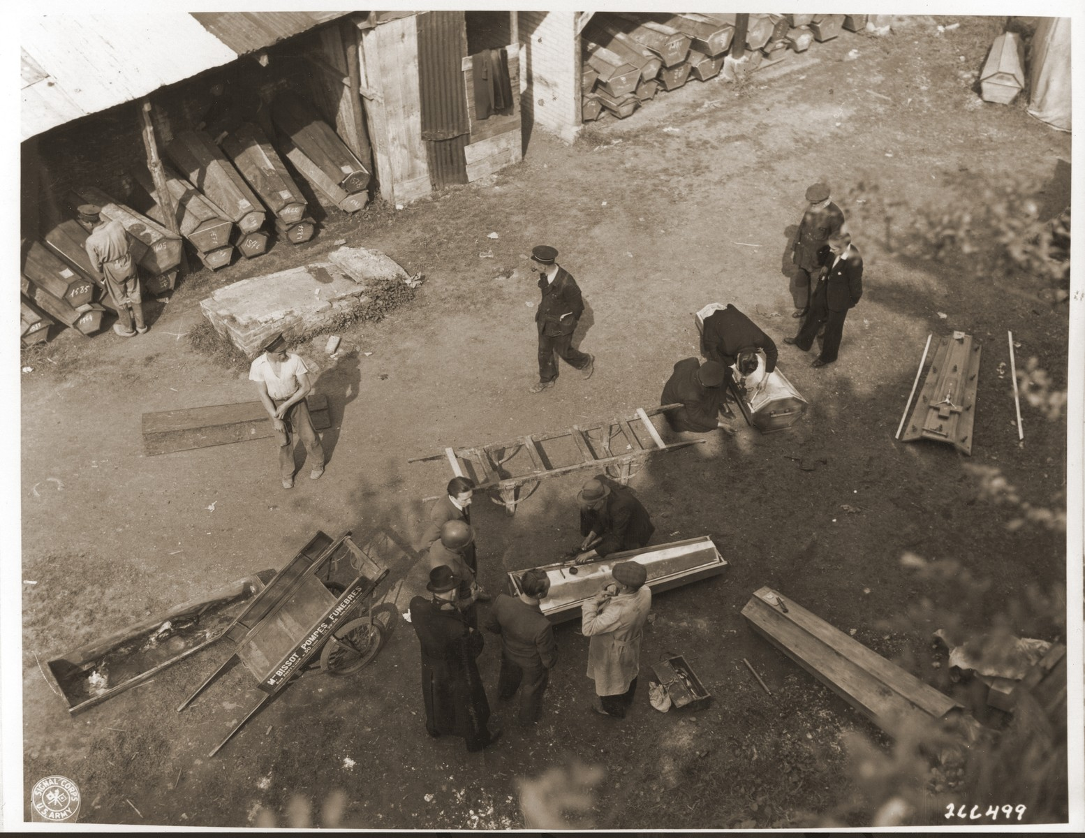 Belgian civilians place the bodies of Belgian political prisoners exhumed from a mass grave into coffins for reburial.
