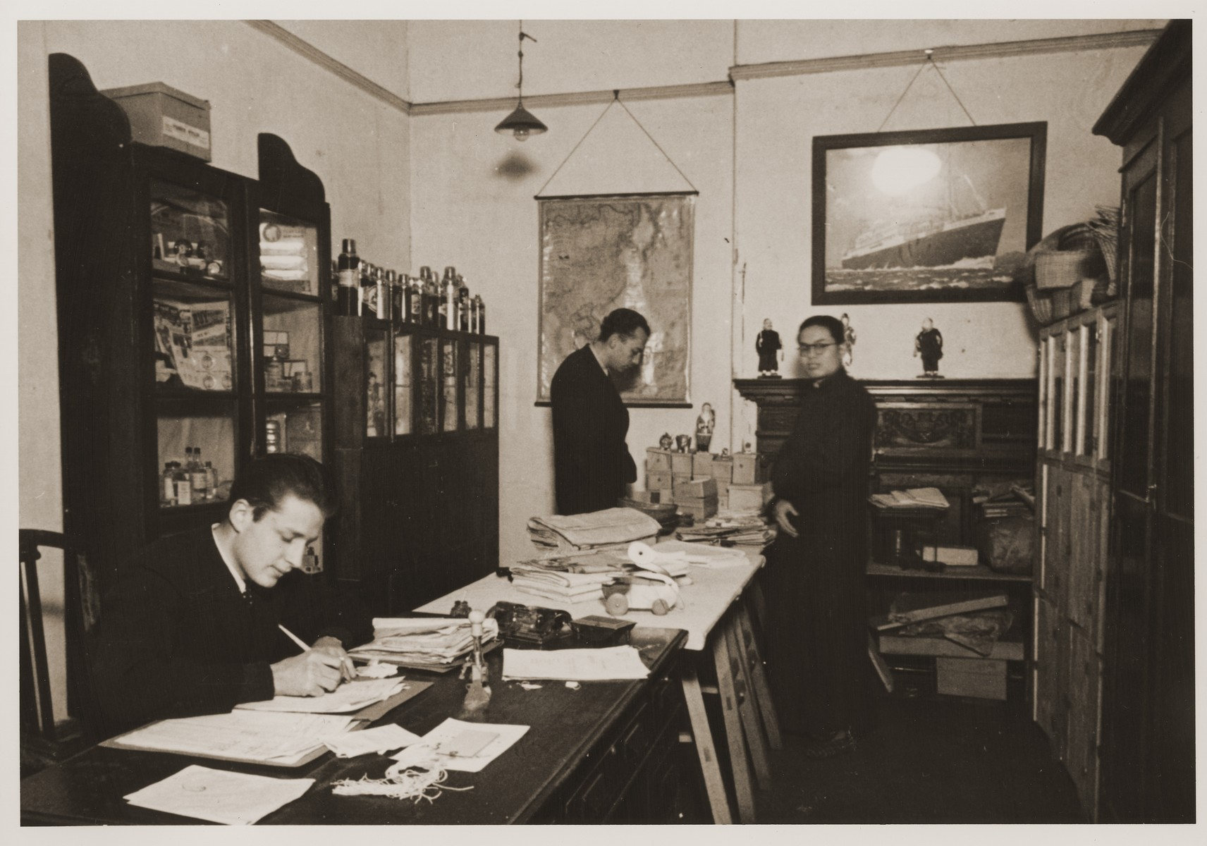 Staff members at work in the offices of the International Committee for European Immigrants in China.  Among those pictured is Eric Goldstaub (seated on the left).