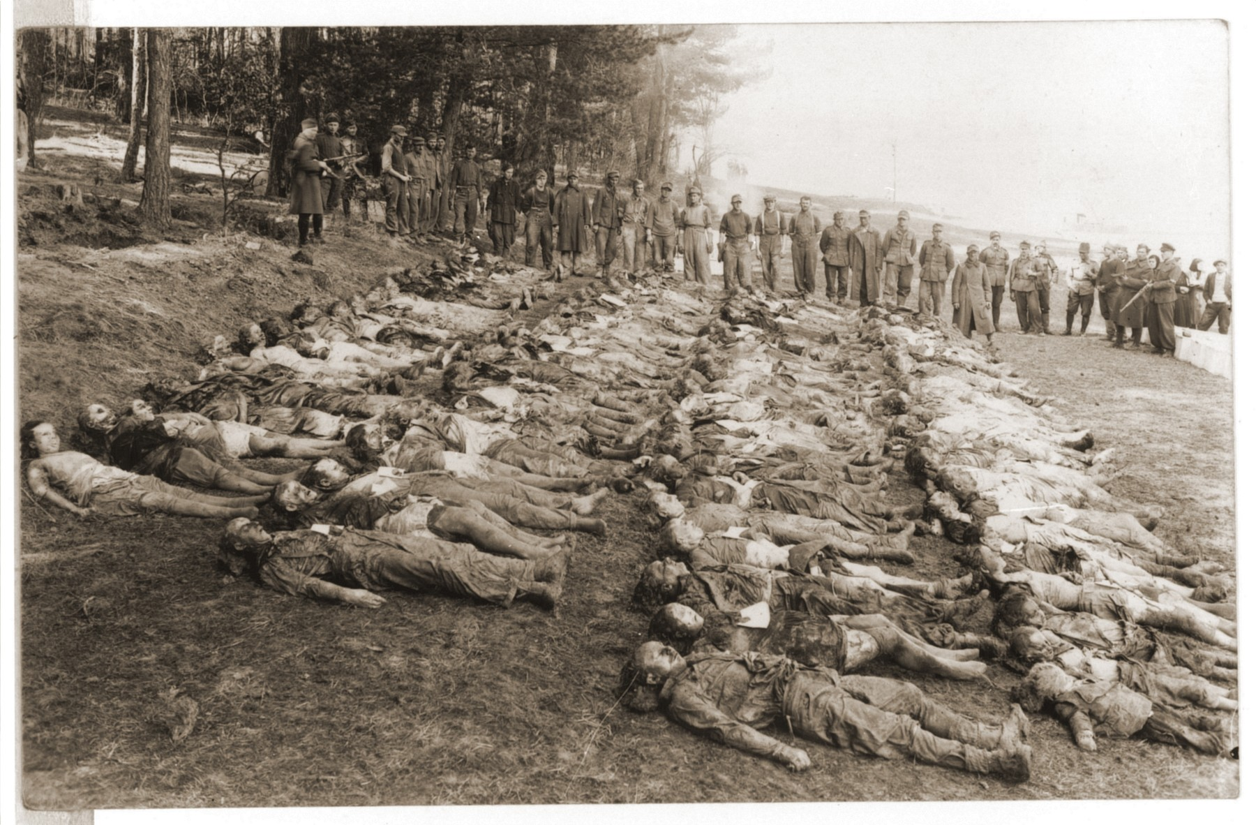German POW's are forced by Soviet guards to rebury corpses exhumed from a mass grave in Czechoslovakia.  The victims consist of men, women, and children.