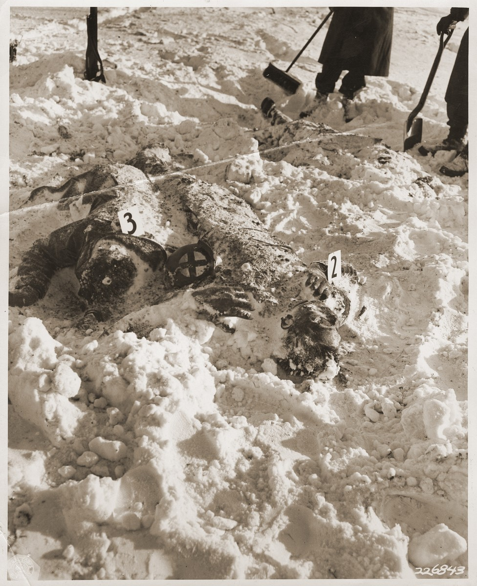 "American soldiers remove snow from the corpses of U.S. troops killed by the SS in the Malmedy atrocity.  The man on the right was an army medic.  The original caption reads ""In the vicinity of Malmedy, Belgium, American soldiers, only portion of bodies seen in picture, prepare to remove for burial the bodies of some of their comrades shot down by Germans in a counter attack, after the American had surrendered, on or about 17 December 1944.  Many Americans were victims of this treachery."""