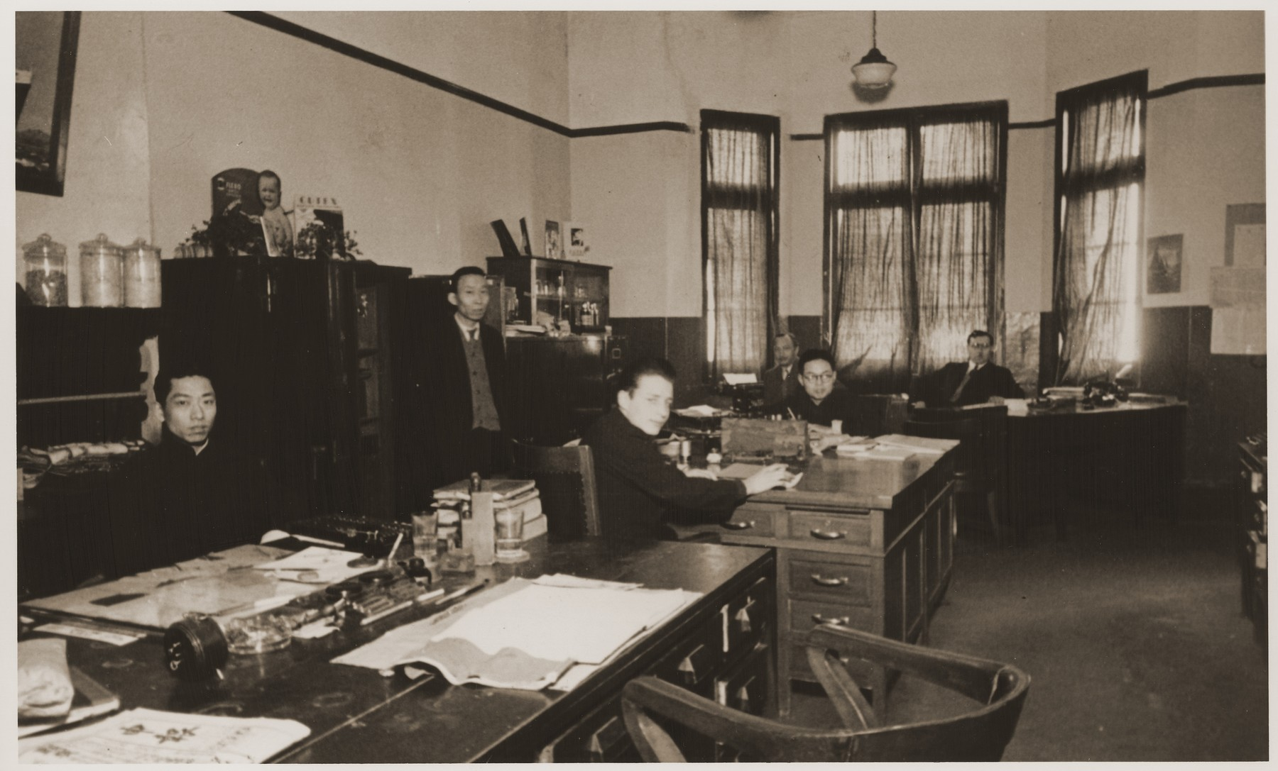 Staff members at work in the offices of the International Committee for European Immigrants in China.  Among those pictured is Eric Goldstaub (seated in the center).  Pictured seated at the desks in the back are Paul Komor, co-founder of  the International Committee for European Immigrants in China, and his brother-in-law, Jack Rogalsky (right, wearing glasses).   Mr. Rogalsky immigrated with his wife and daughter to Toronto in 1949, and died in 1974.