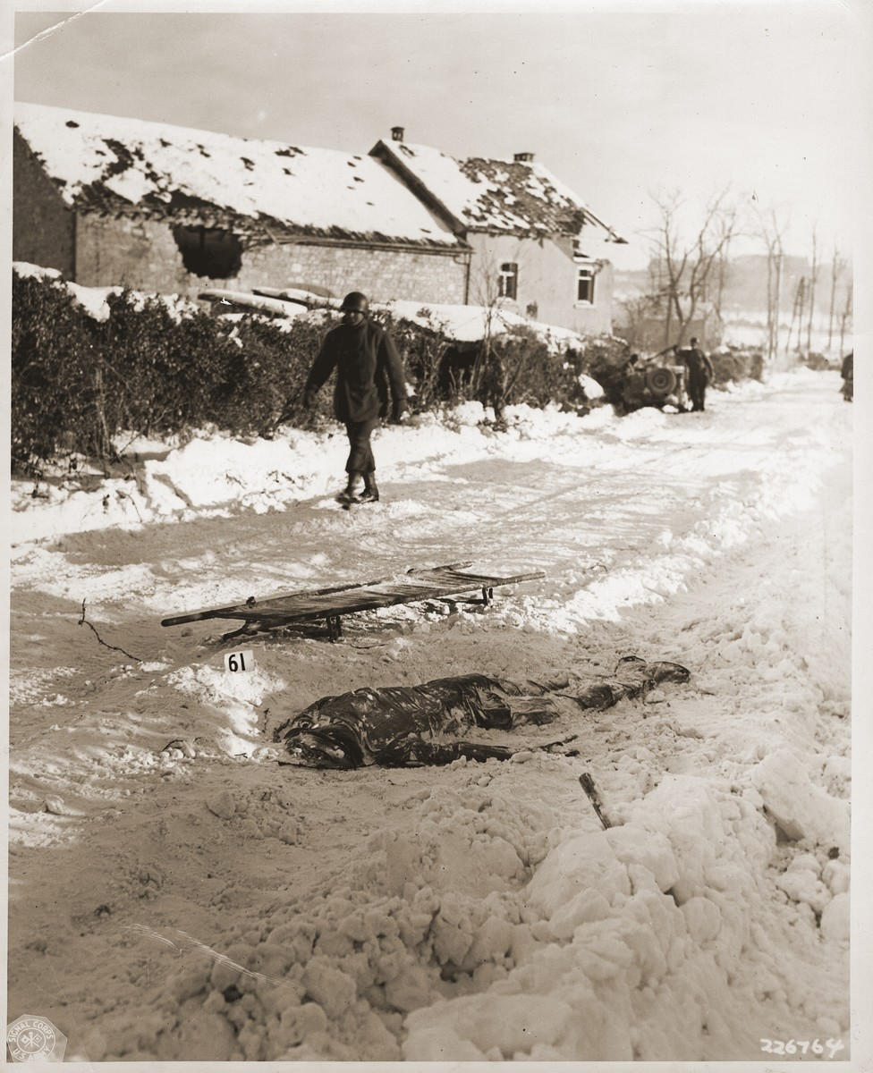 """An American soldier walks past the corpse of an American soldier killed by the SS and then run over by a tank during the Malmedy atrocity.  The original caption reads """"American soldiers who were shot by German troops after they had surrendered were left where they had fallen in the snow.  A sled is near the body of this soldier with his number in the snow near it.  These German atrocities were committed on or about the 17th December 1944 in the vicinity of Five Points, near Malmedy Belgium."""""""