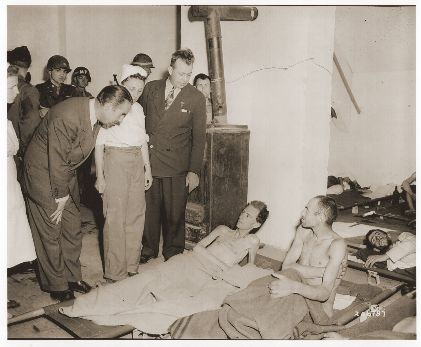 U.S. Congressman Everett M. Dirkson visits former concentration camp prisoners recuperating in an Allied hospital in Linz during his world tour to determine the financial needs of federal bureaus.