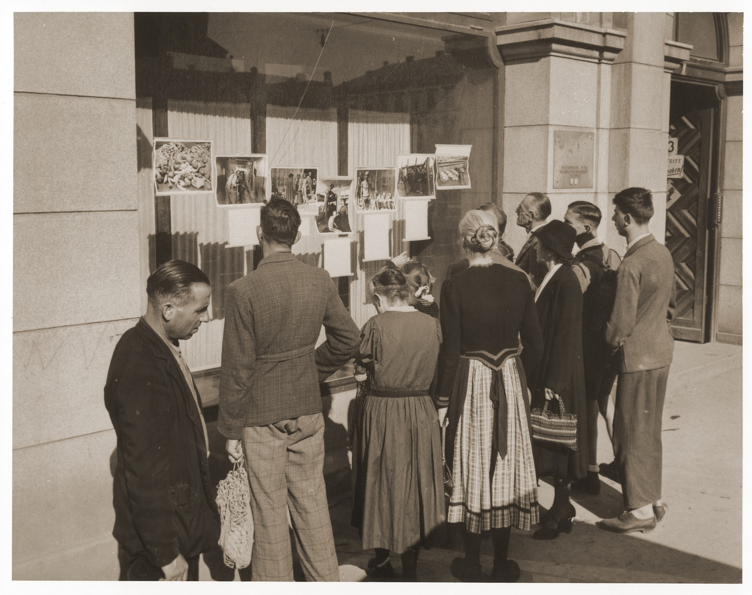 Austrian civilians view a display of photographs mounted in the window of a building in Linz showing Nazi atrocities in various concentration camps.   The photographs were supplied by the Information Service Branch of the Psychological Warfare Division, Supreme Headquarters Allied Expeditionary Force.  The displays were shown in all American held districts of Austria.
