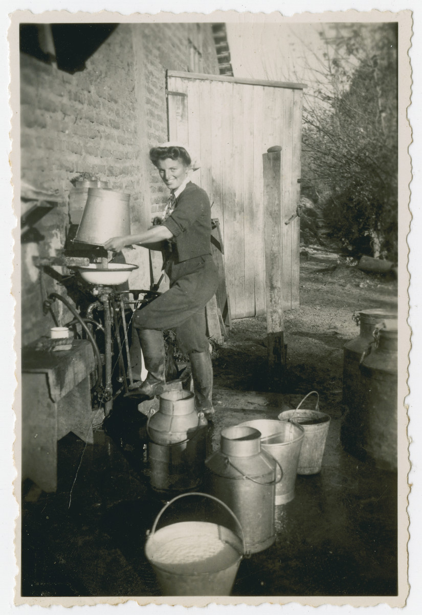 """Photograph from an album entitled, """"Hacshara Kidma Chile,""""  documenting life on a postwar Shomer Hatzair Zionist agricultural collective in Chile.  A young woman empties a bucket of fresh milk into a cream separator (?).   The inscription on the album page (in Spanish) reads, """"Aaron's invention, number 11753."""""""