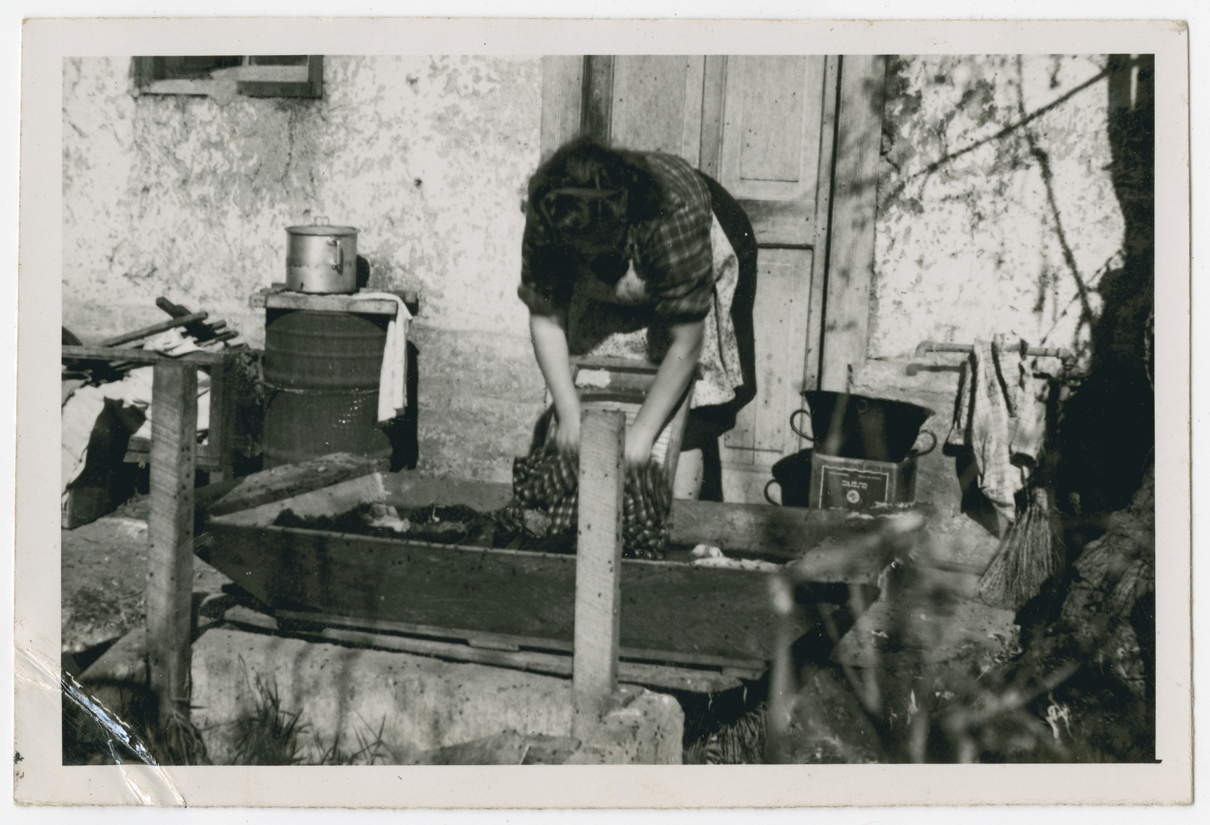 "Photograph from an album entitled, ""Hacshara Kidma Chile,""  documenting life on a postwar Shomer Hatzair Zionist agricultural collective in Chile.  A young woman washes clothing on a washboard. The inscription on the album page reads, ""La Monja."""