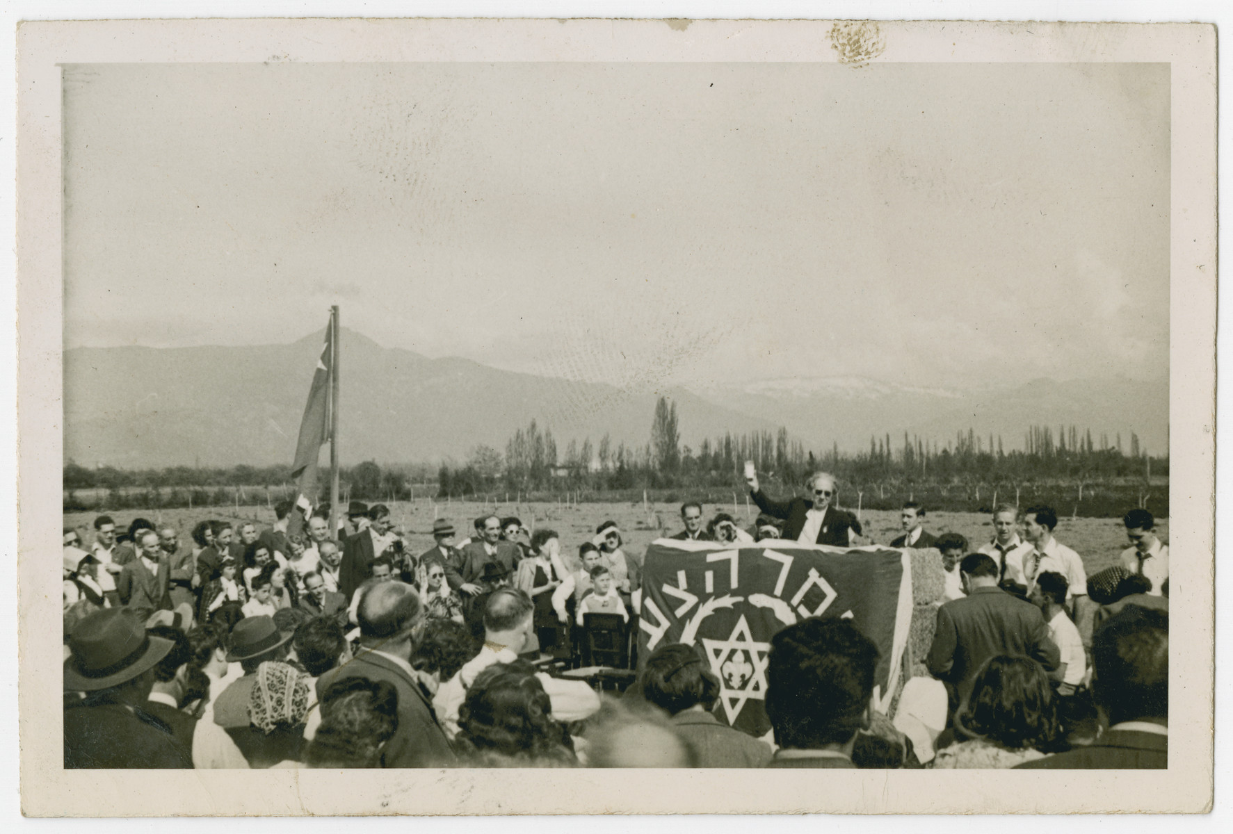 """Photograph from an album entitled, """"Hacshara Kidma Chile,""""  documenting life on a postwar Shomer Hatzair Zionist agricultural collective in Chile.  A speaker addresses the crowd at the inauguration of the hachshara."""