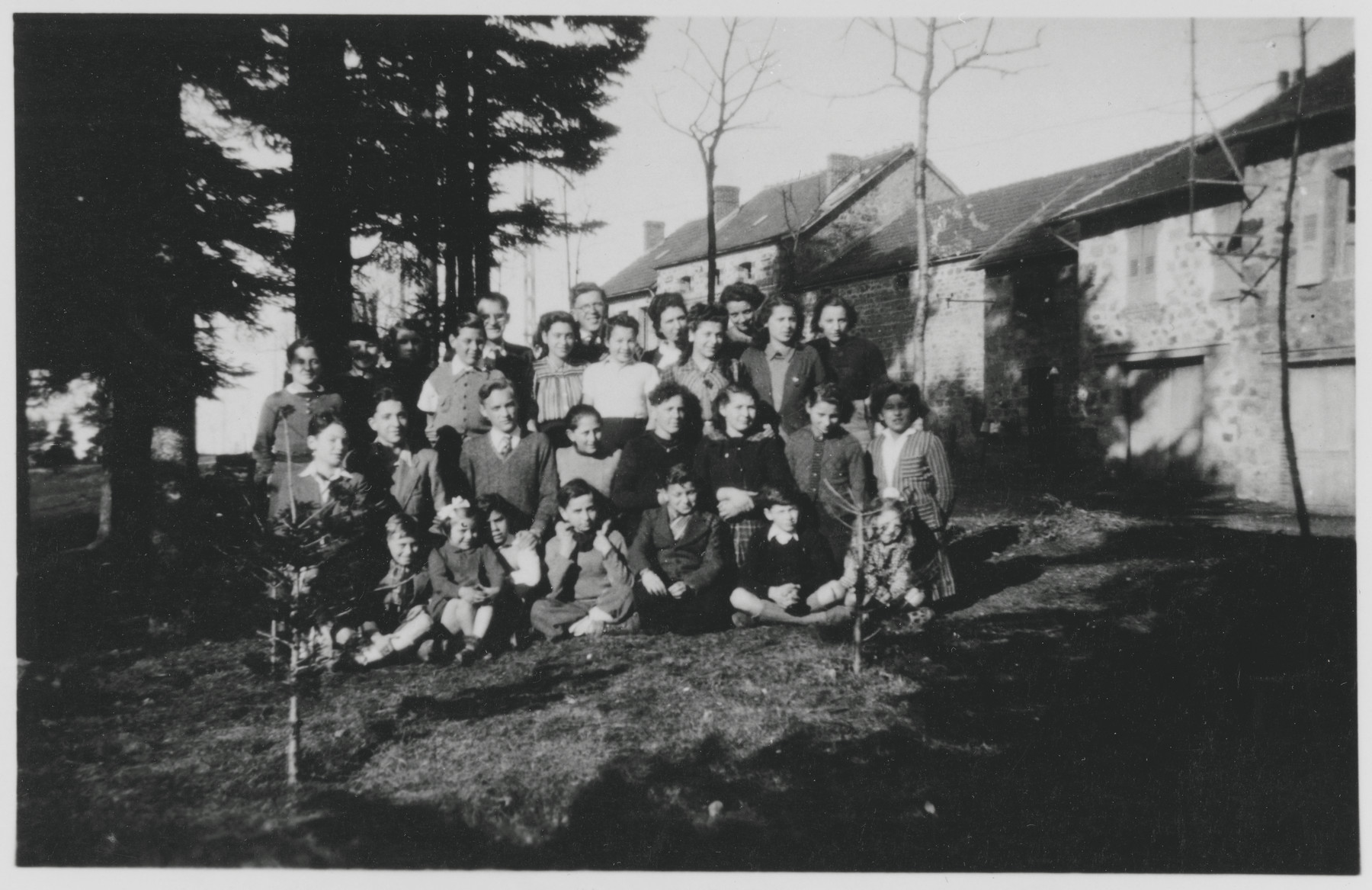 Group portrait of Jewish and non-Jewish refugee children sheltered in various public and private homes in Le Chambon-sur-Lignon during World War II with some of the French men and women who cared for them.  Among those pictured are: Daniel Trocmé (top row, center wearing glasses), Edouard Theis (top row, to the left of Daniel Trocmé), Peter Feigl (third row from the front, second from the left), Amede Dutry (third row from the front, far left), Kurt Grossman (second row from the front, far left), Jean Speigel (second row from the front, second from the left), Simone Fullenbaum (second row from the front, far right), Paul Fogelman (front row, center).
