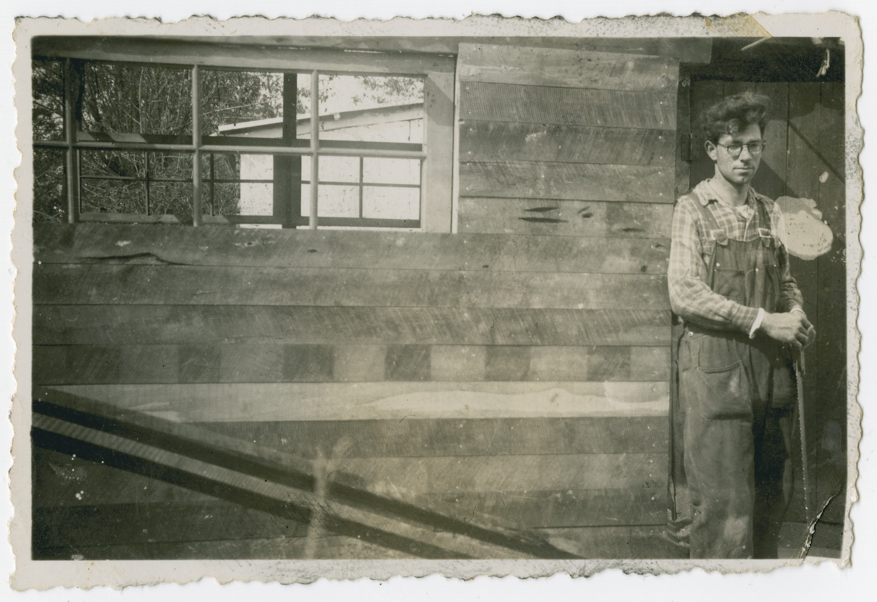 "Photograph from an album entitled, ""Hacshara Kidma Chile,""  documenting life on a postwar Shomer Hatzair Zionist agricultural collective in Chile.  A young Jewish man wearing overalls stands next to a building."