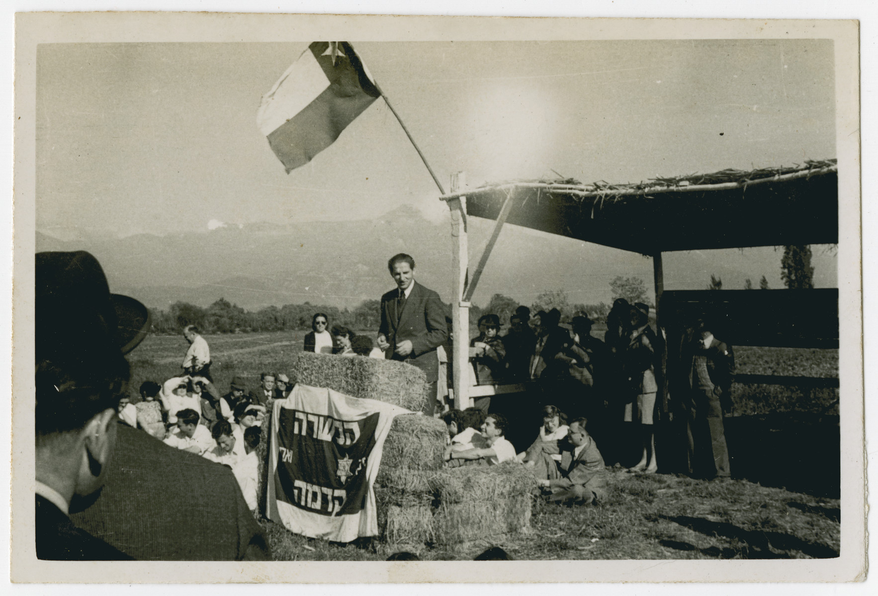 "Photograph from an album entitled, ""Hacshara Kidma Chile,""  documenting life on a postwar Shomer Hatzair Zionist agricultural collective in Chile.  A man addresses the crowd from a strawbale podium, under the Chilean flag.  The inscription on the back reads, ""Jose Tchormitzki Meseico.""  The Hebrew banner says Hachshara Kedma."