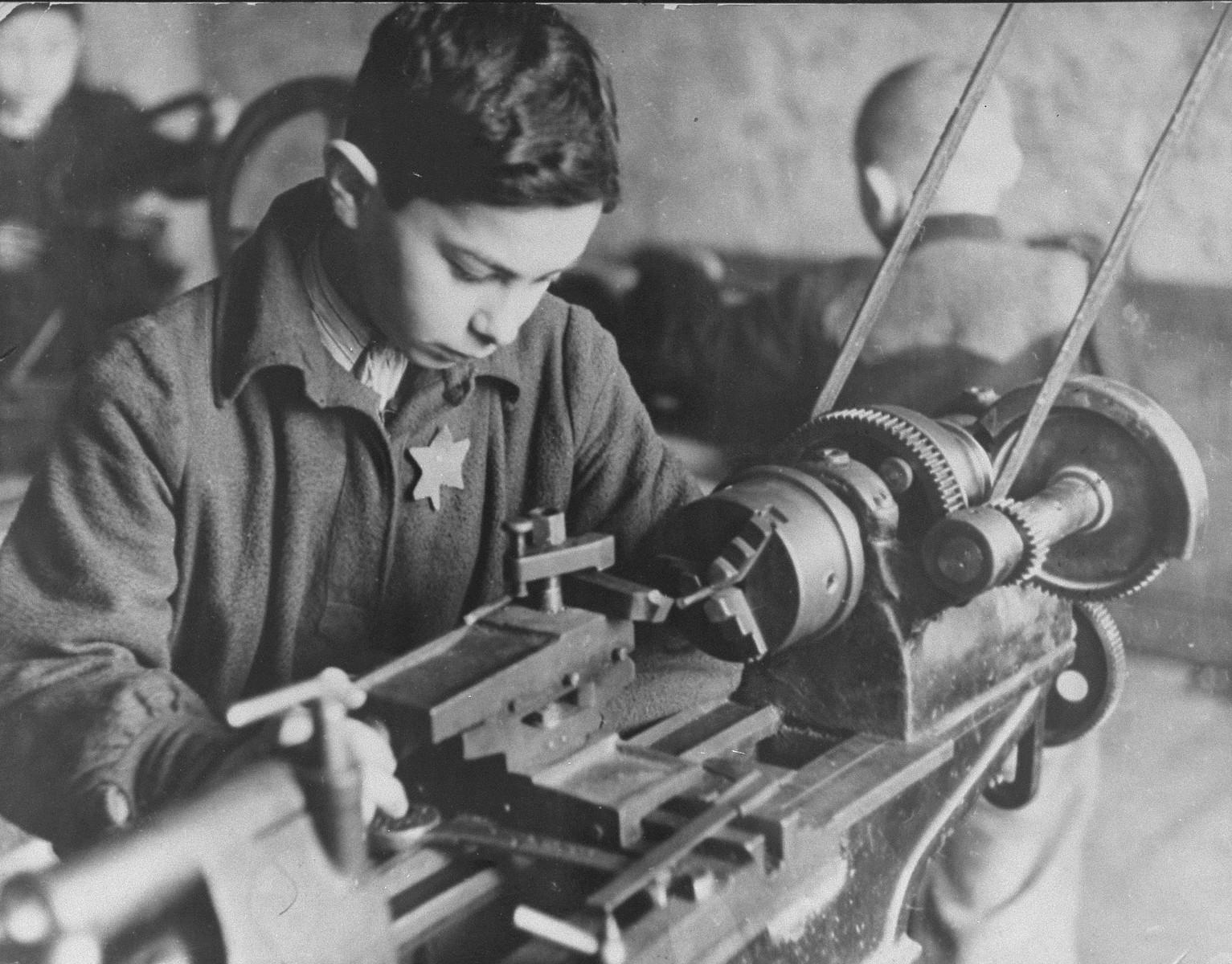 A boy works at a machine in a Kovno ghetto workshop.  Pictured is Yakob Vizgordiski.