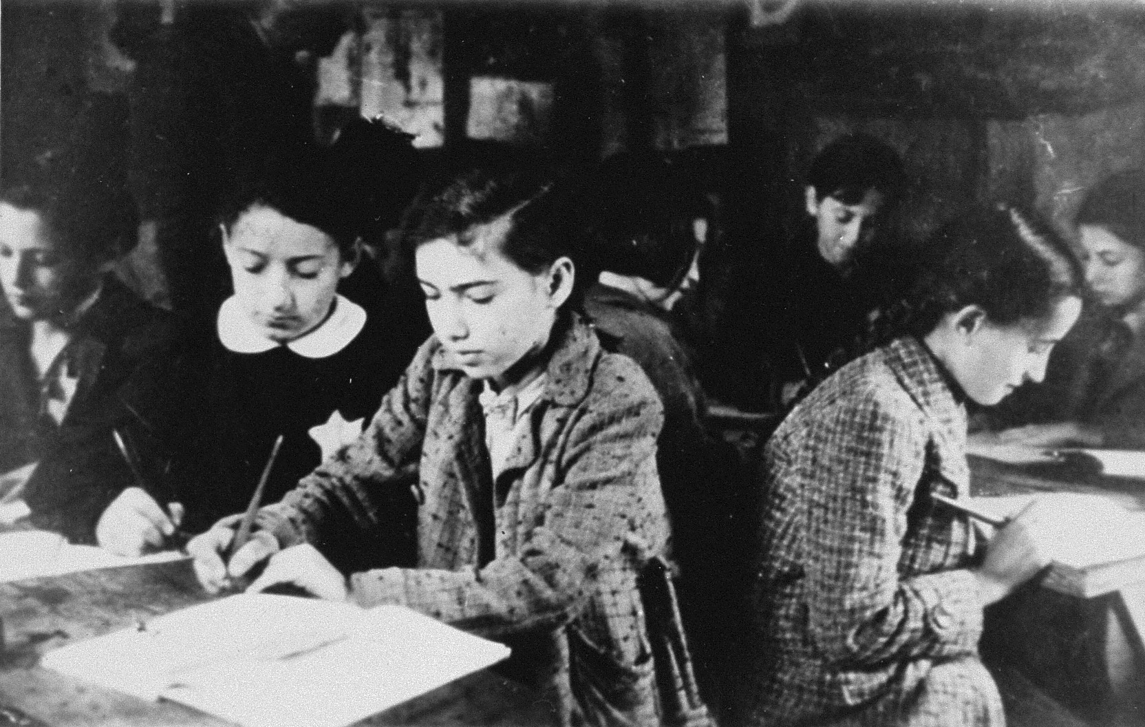 Children studying in a clandestine school in the Kovno ghetto.    Classes were held in a stable at 101 Kriktshukaitchiu Street.  Among those pictured are Taiba Leibaite (far left), Basia Leibaite (second from the left), David Ackerman Falahi (in the back),and teacher Shmuel Rozental (in the background).