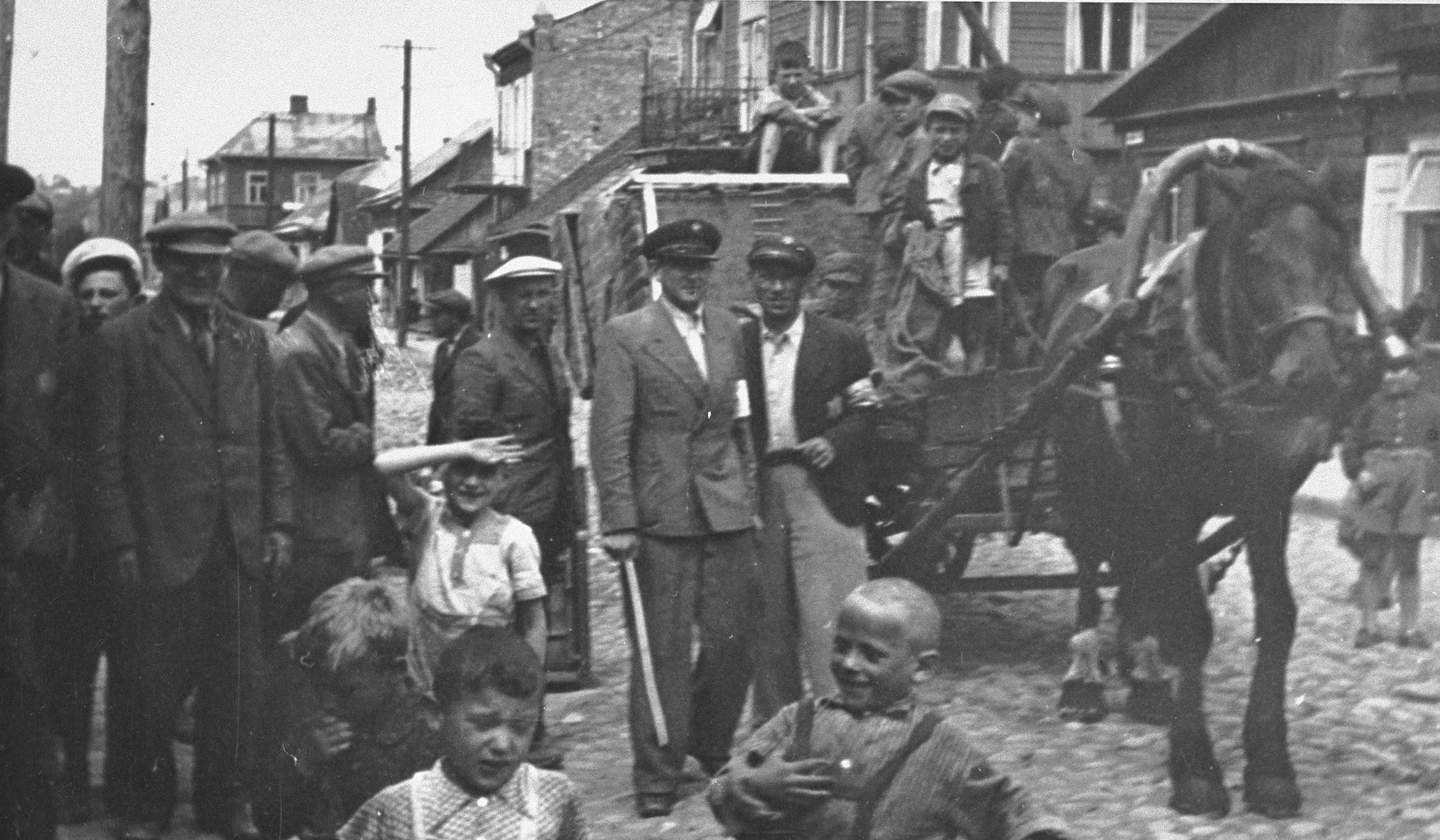 Street scene in the Kovno ghetto.    The wagon is transporting mattresses to former cinema being used to house Jews arriving to the ghetto from Zezmer.