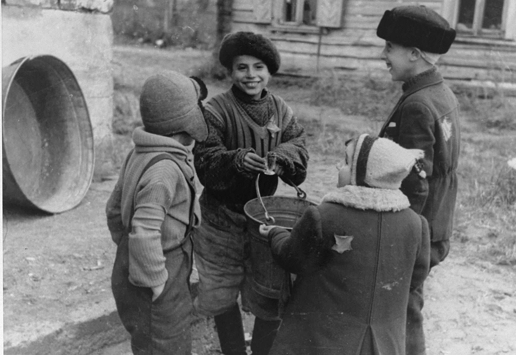 Four Jewish children converse outside in the Kovno ghetto.